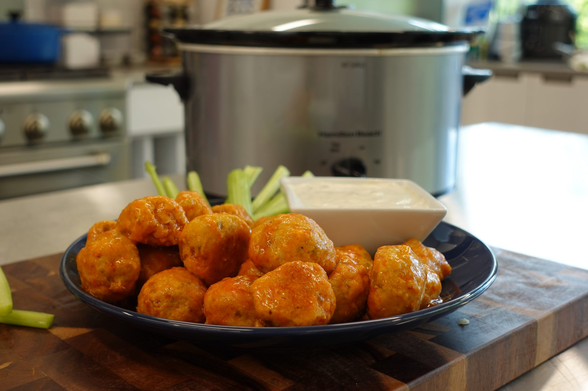 buffalo chicken meatballs in front of silver slow cooker