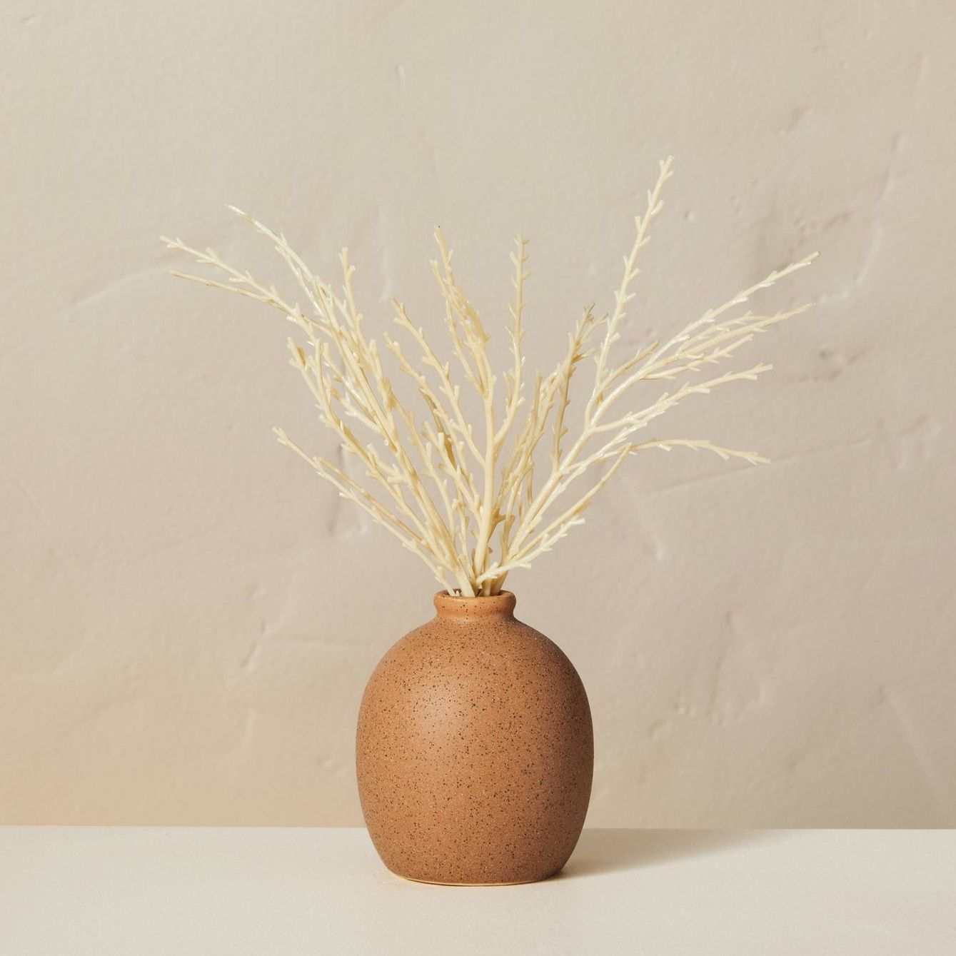 brown vase with dried wheat arrangement