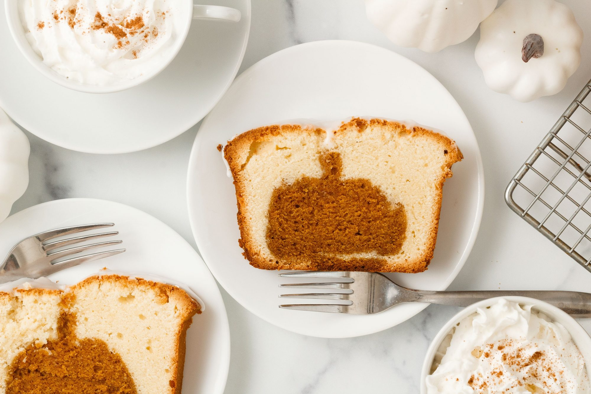 overhead shot of a slice of pound cake sliced to reveal a pumpkin-shaped pumpkin spice cake baked into it.