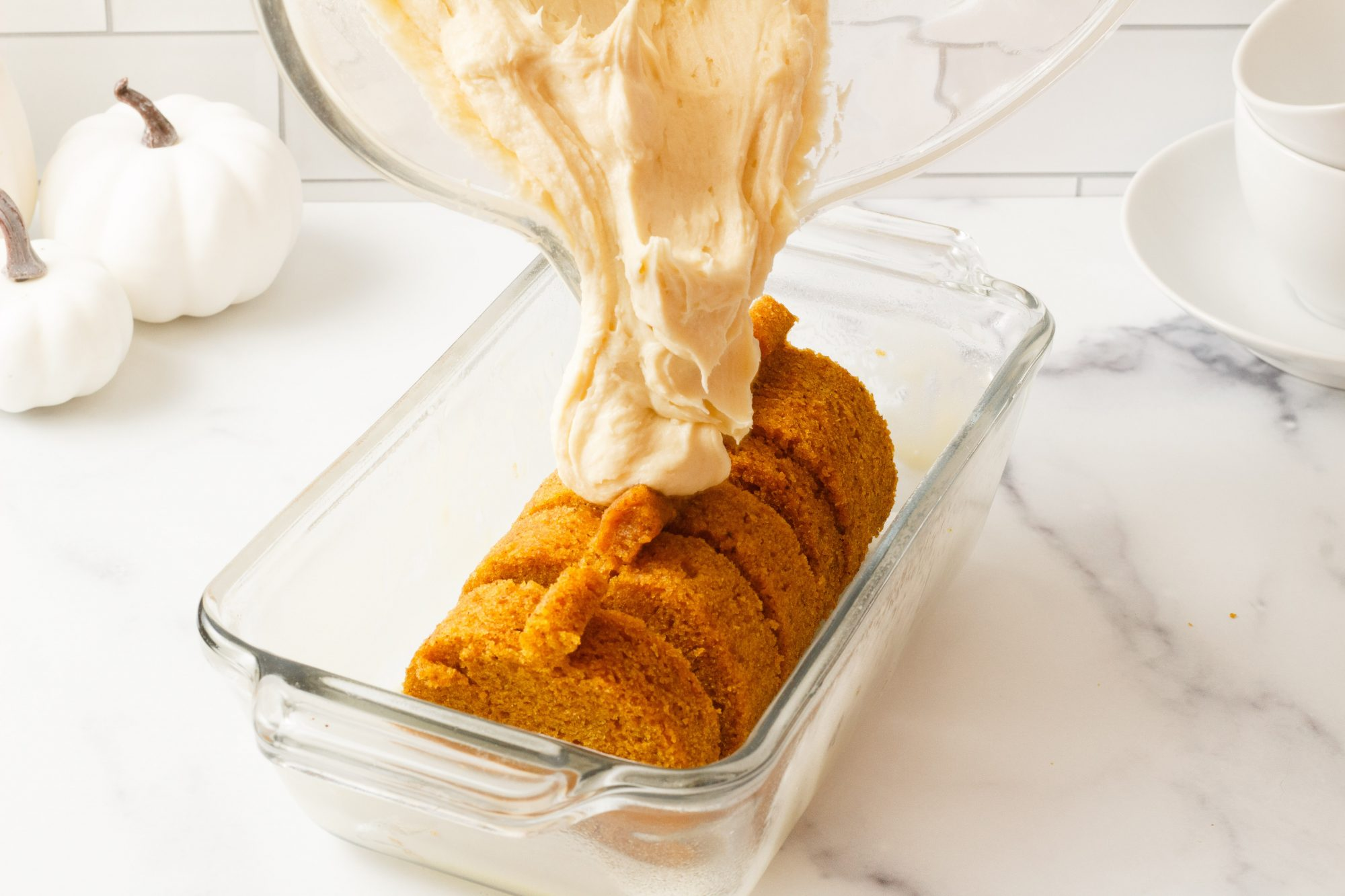 pouring pound cake batter over pumpkin-shaped pumpkin spice cake cutouts lined up in a glass baking dish