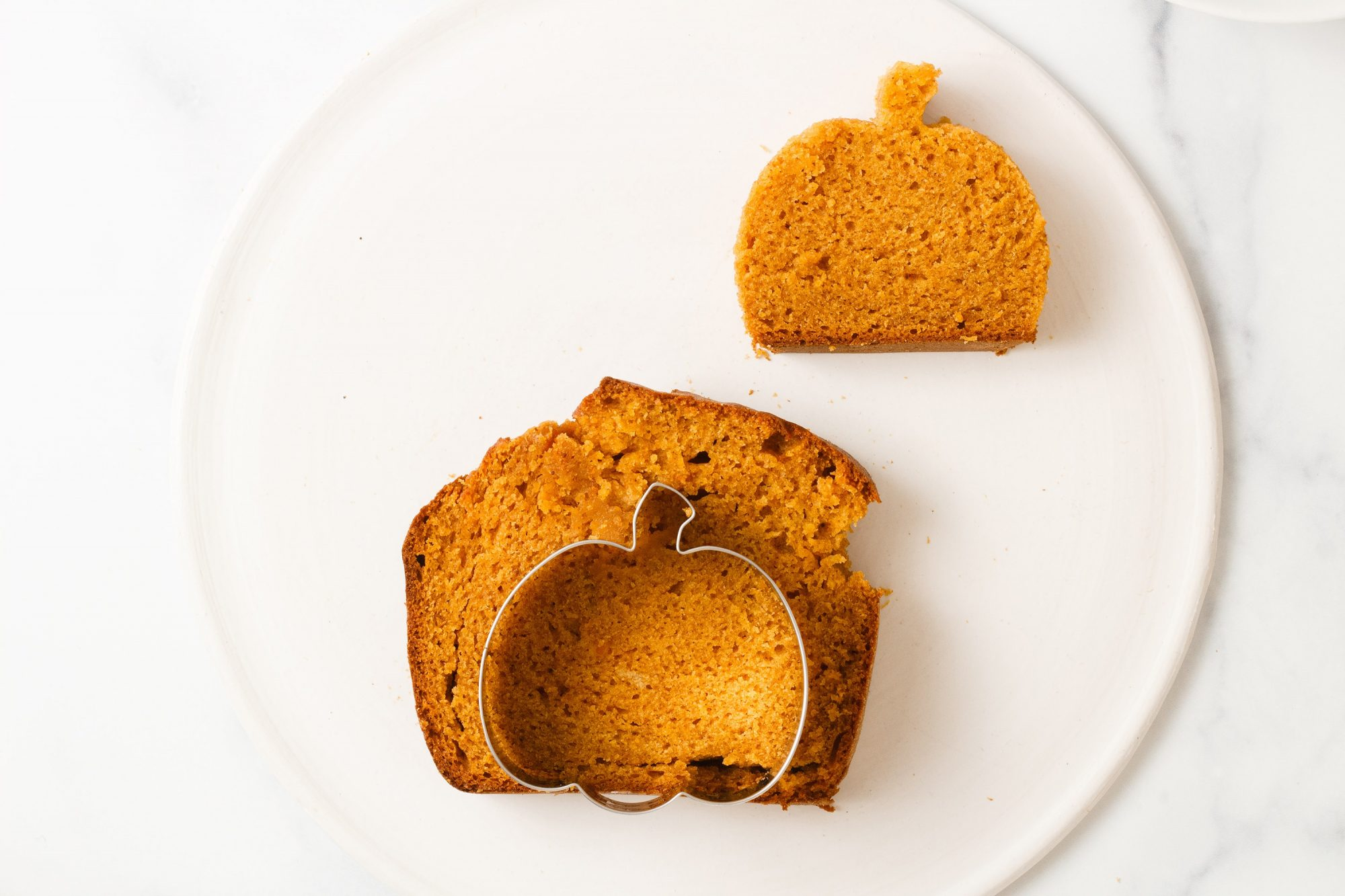 using a pumpkin-shaped cookie cutter to cut out pumpkin shapes from slices of pumpkin spice cake