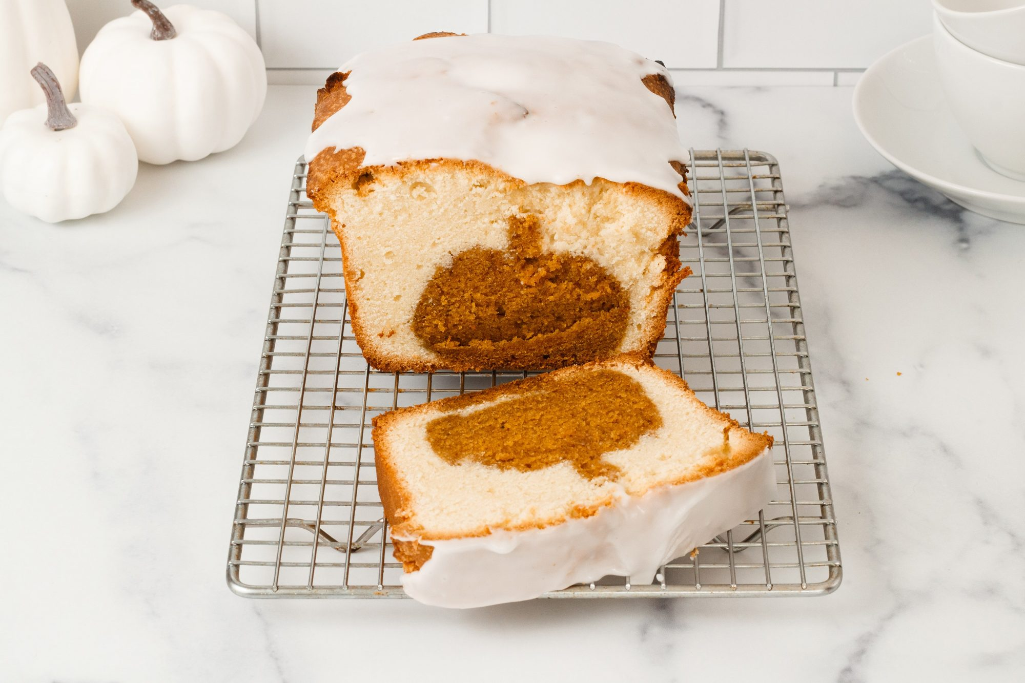 loaf of pumpkin spice surprise cake topped with confectioner's sugar glaze and sliced to revel a hidden pumpkin-shaped pumpkin spice cake baked into it.