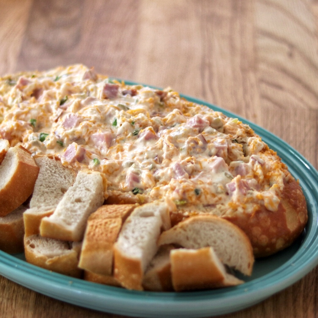 creamy cheese and ham topping on a french bread half on a blue plate