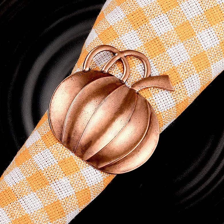 bronze pumpkin shaped napkin ring over yellow gingham napkin on a black plate