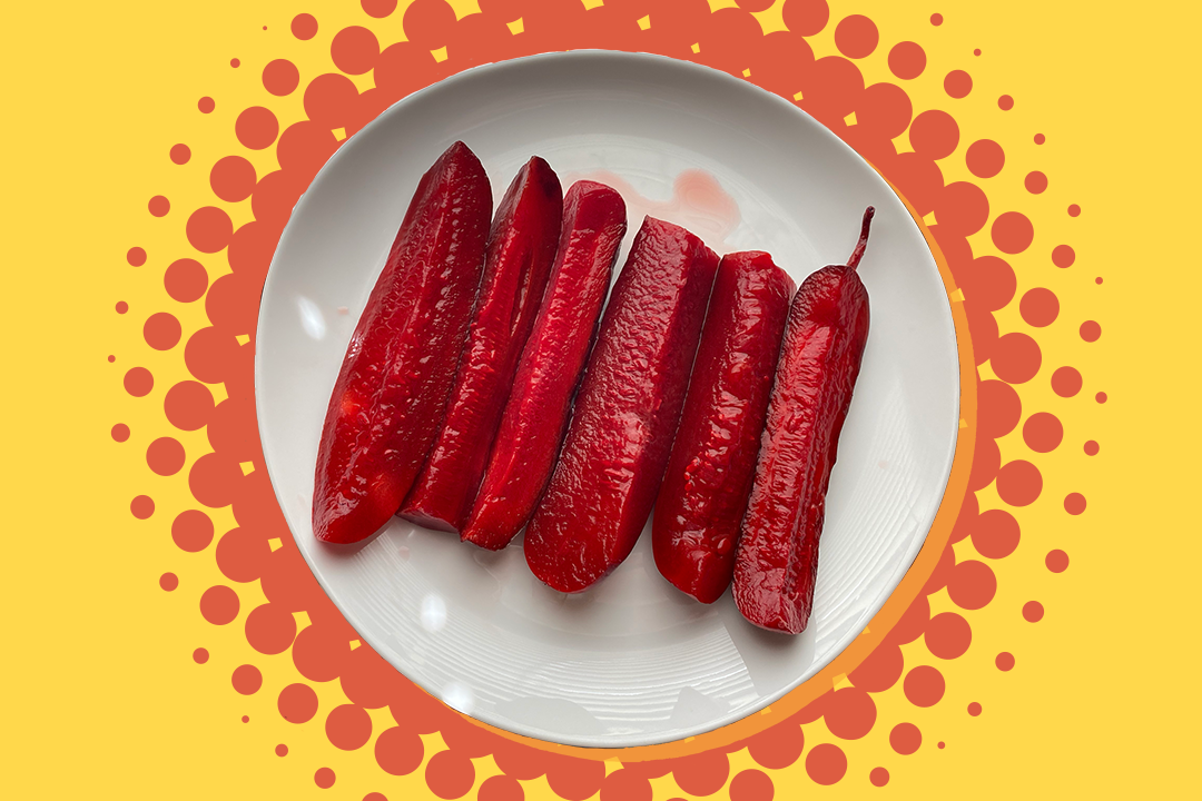 red koolaid pickles on a white plate on a background with an orange burst and yellow background