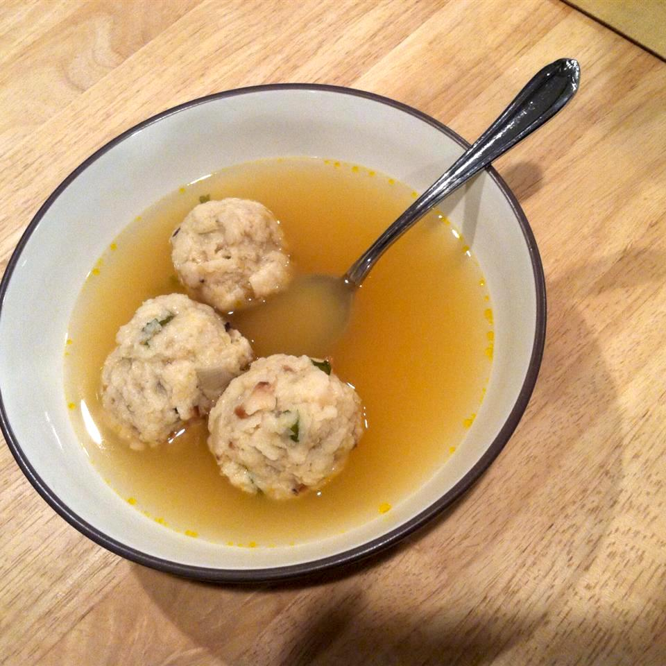 bowl of soup with clear broth and meat balls