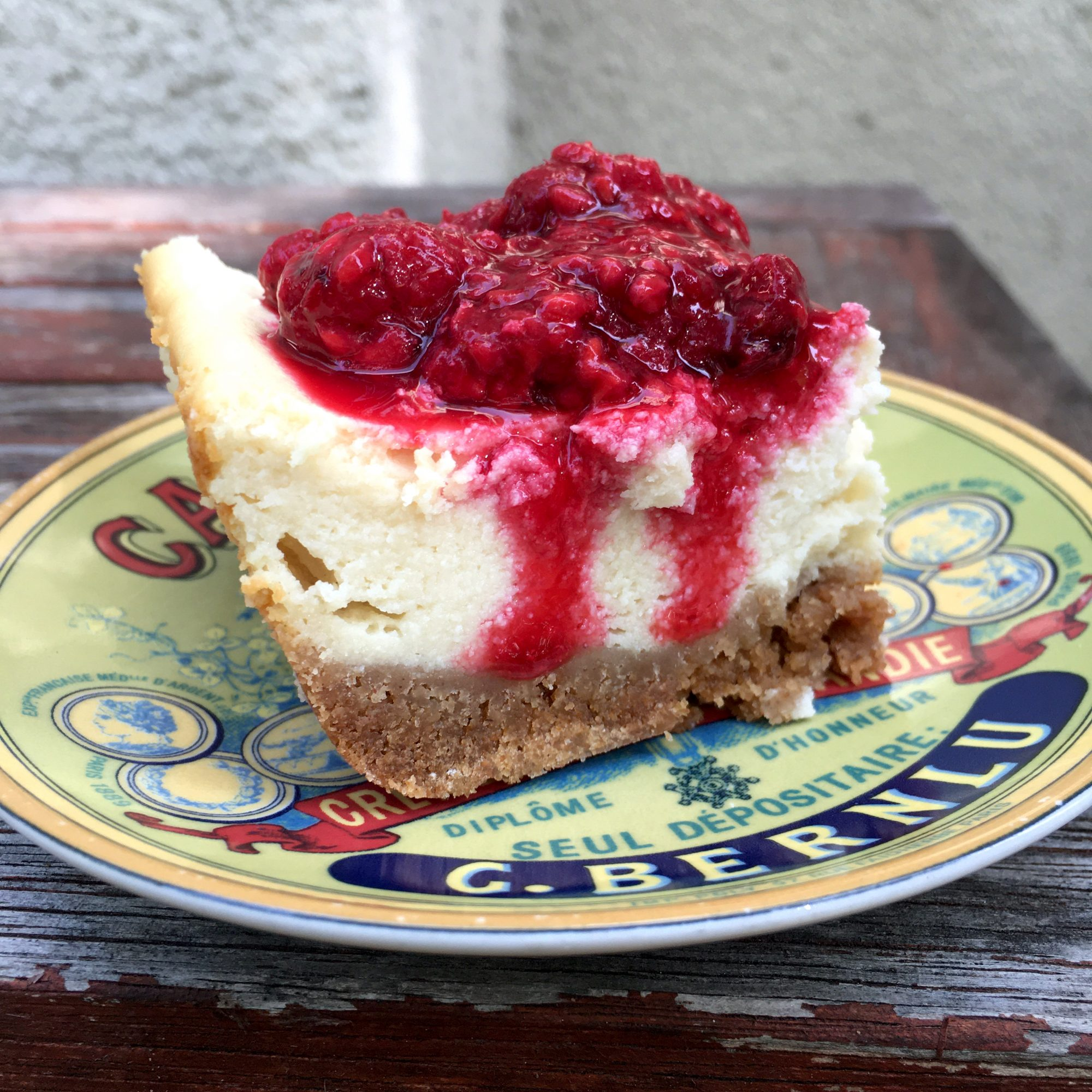 thick slice of cheesecake with syrupy raspberry topping
