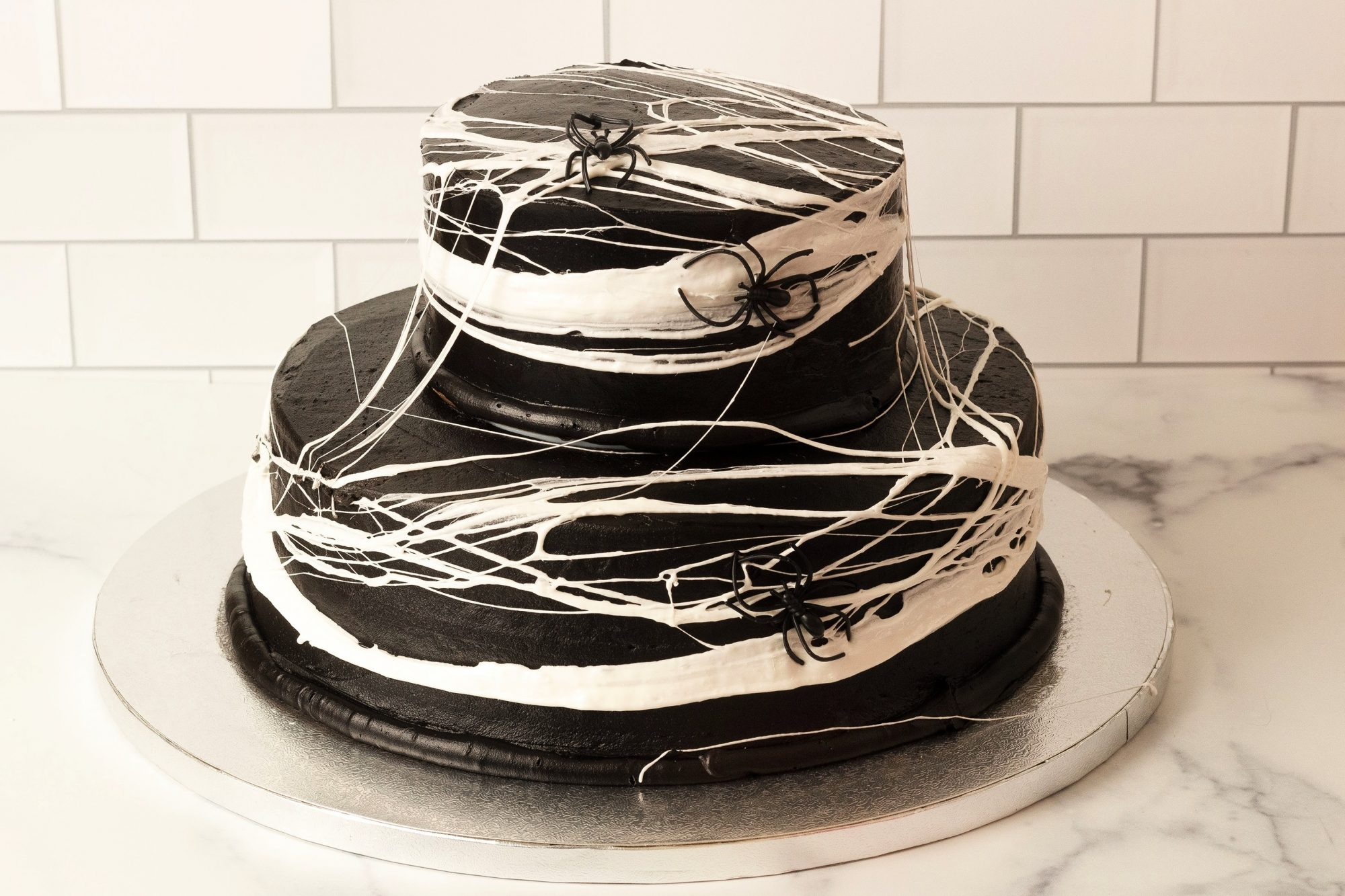two-tiered cake with dark chocolate frosting and marshmallow spider web decoration