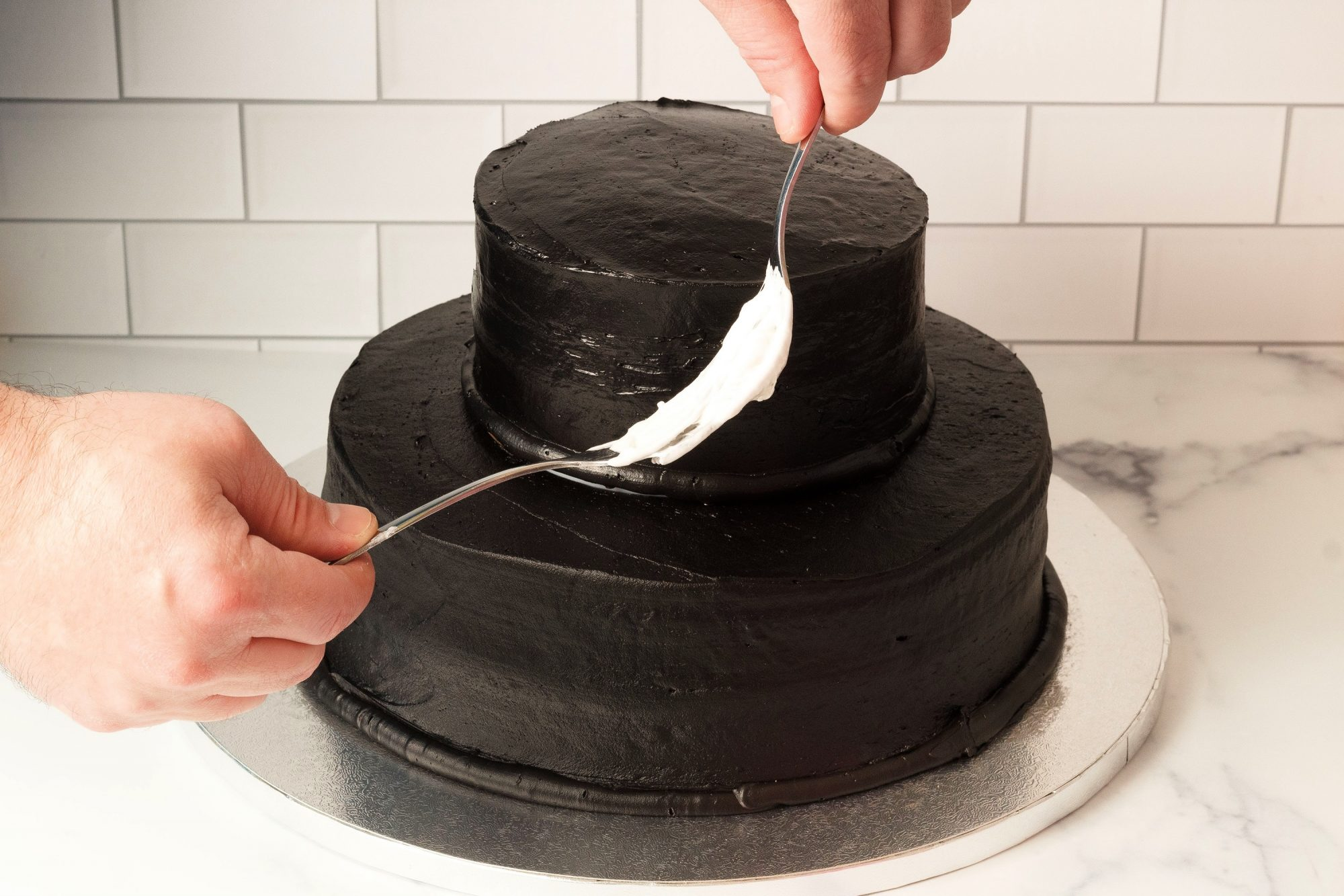 using a pair of forks to apply melted marshmallow onto a two-tiered dark chocolate cake to form a spiderweb decorations