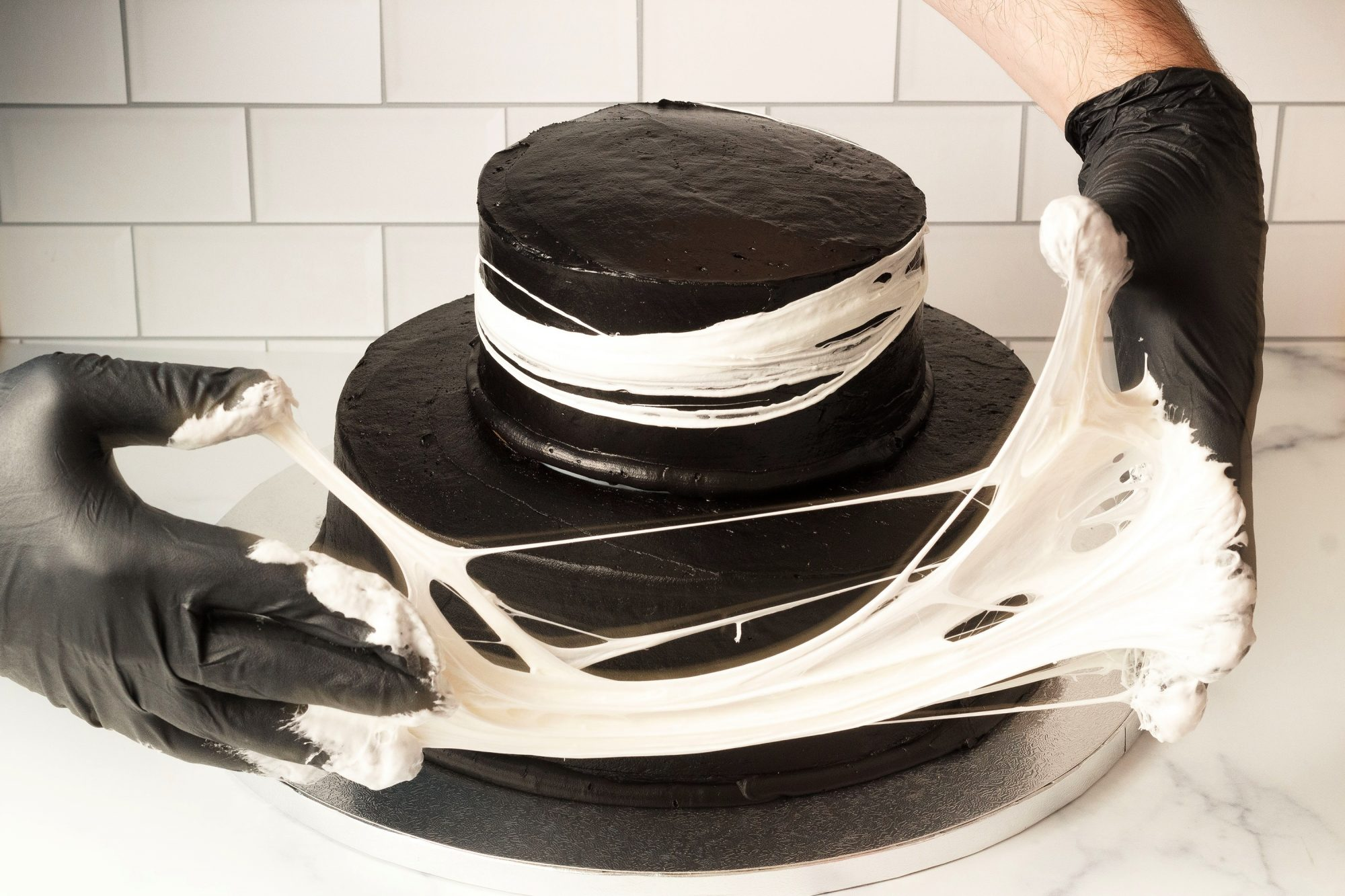 gloved hands stretching melted marshmallow to form a spiderweb decoration on a two-tiered dark chocolate cake for Halloween