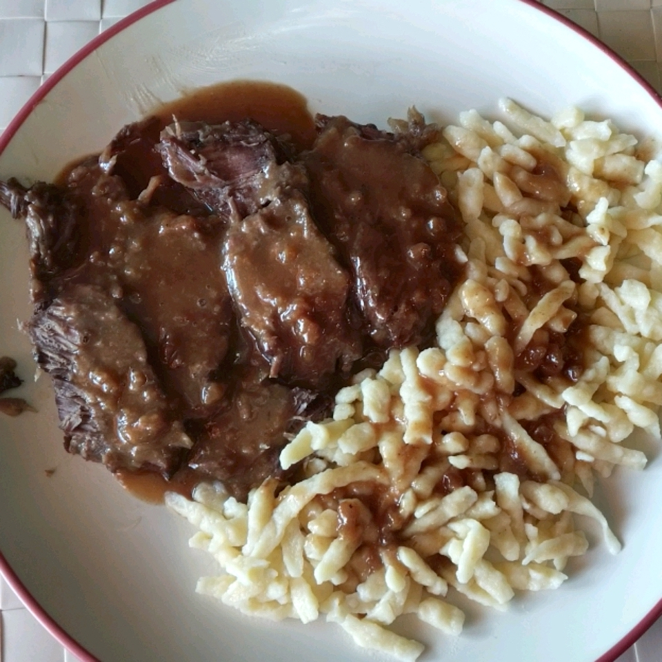 beef with gravy on a plate with noodles