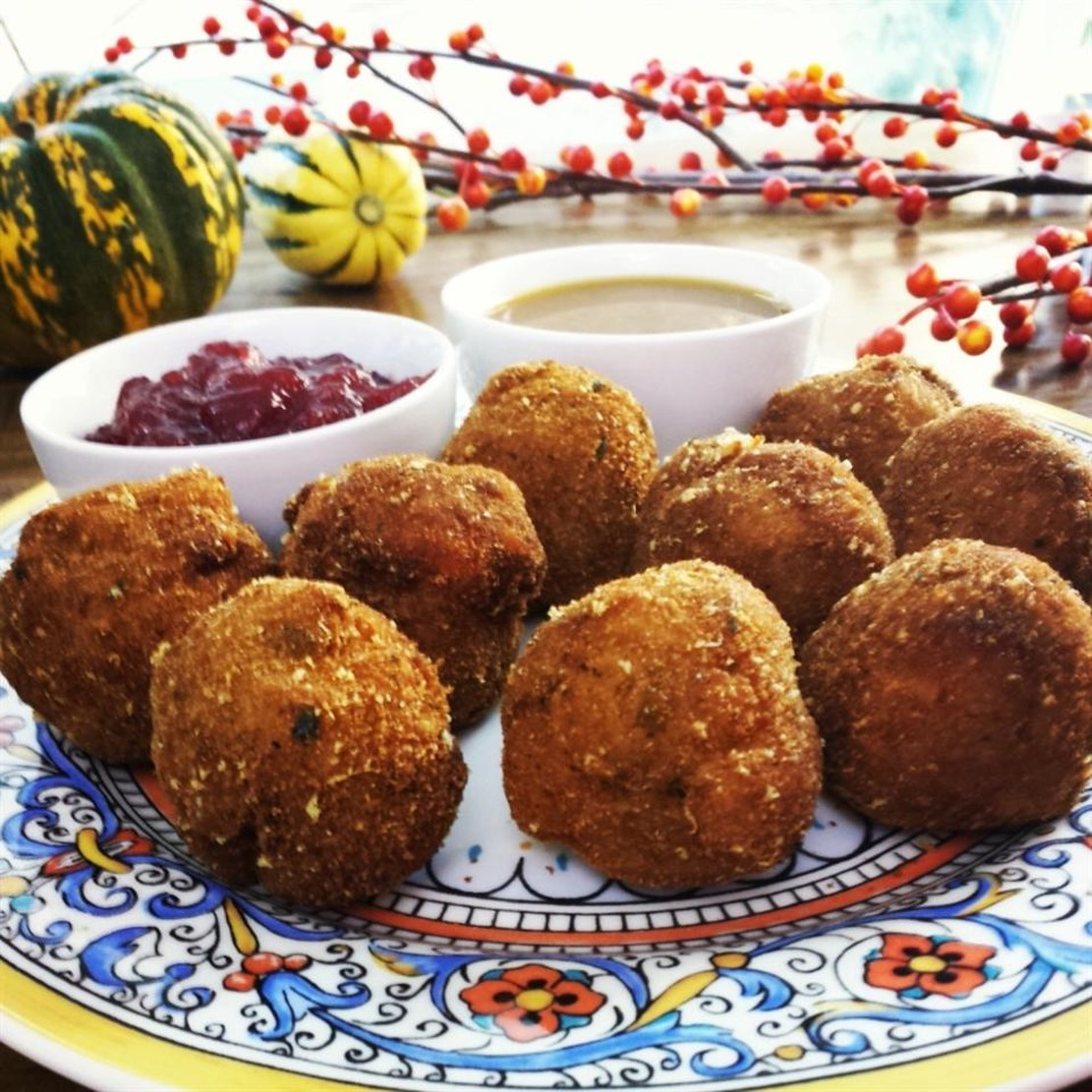 deep fried stuffing balls on a decorative plate with cranberry sauce for dipping
