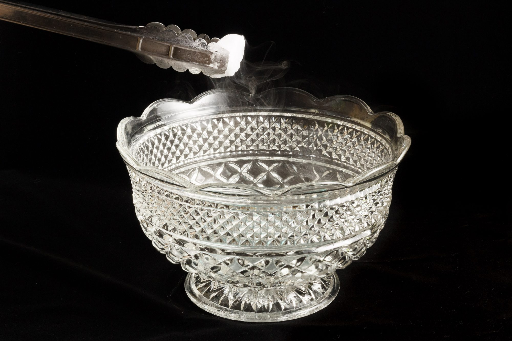 Using metal tongs to place dry ice in decorative punch bowl