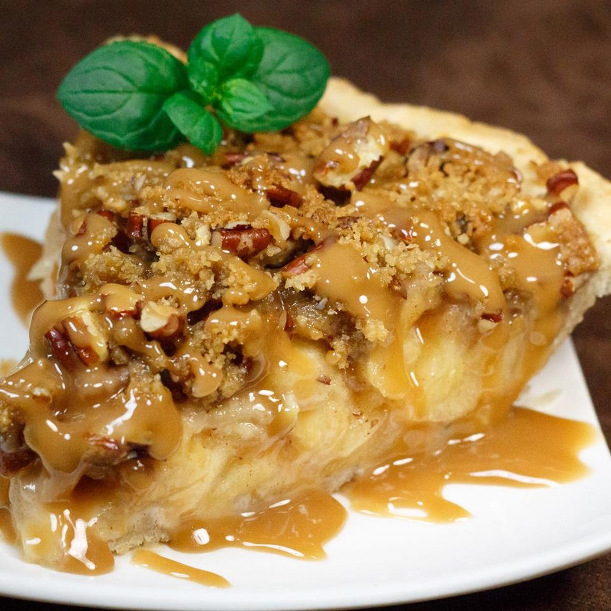 a slice of apple streusel pie with caramel sauce on top