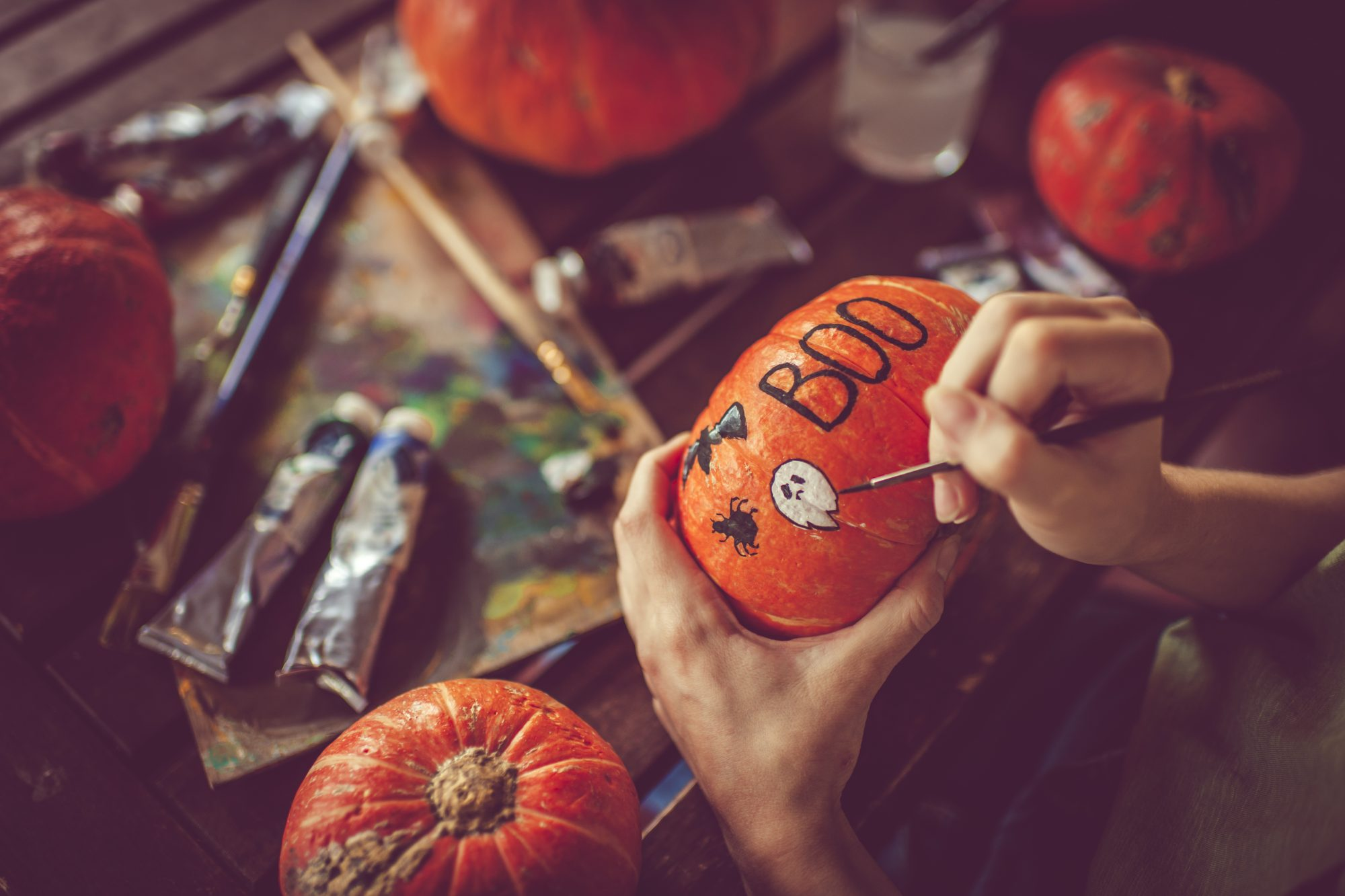 Young girl painting on pumpkin in Halloween