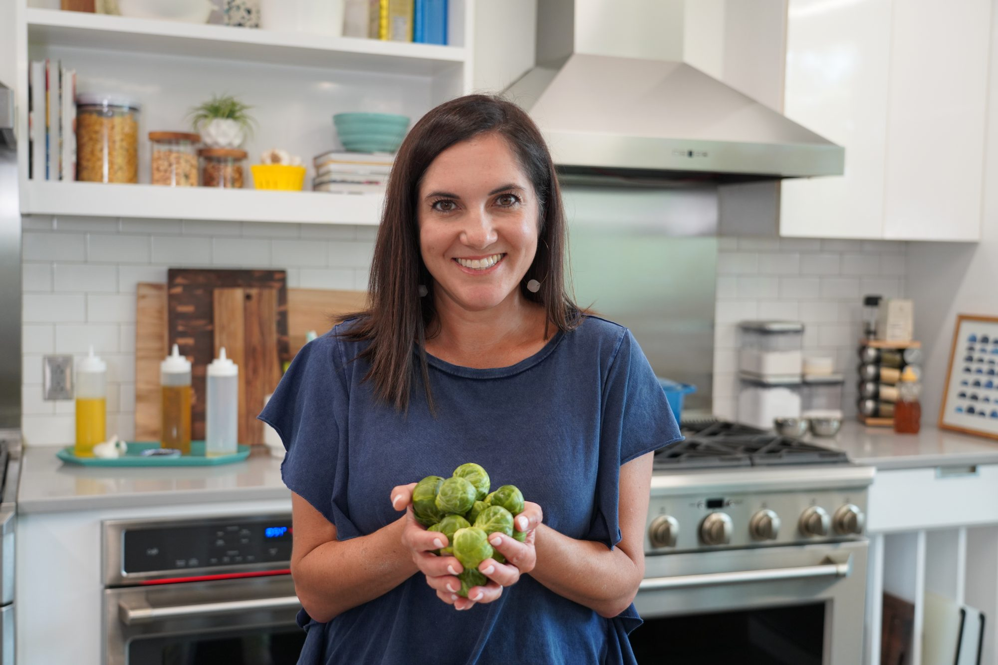 Nicole McLaughlin holding Brussels Sprouts in kitchen
