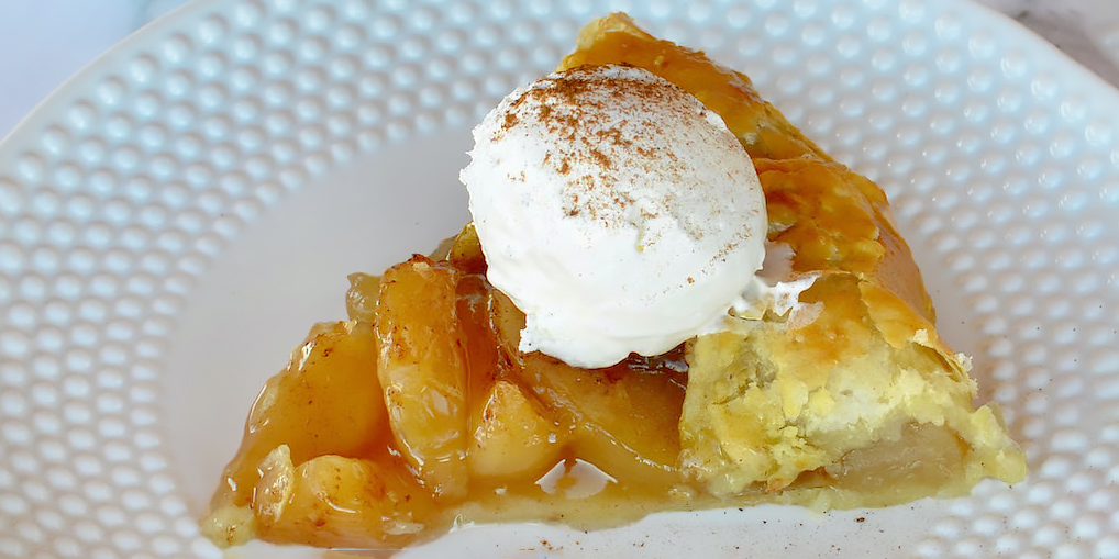 single plated slice of an apple galette topped with whipped cream