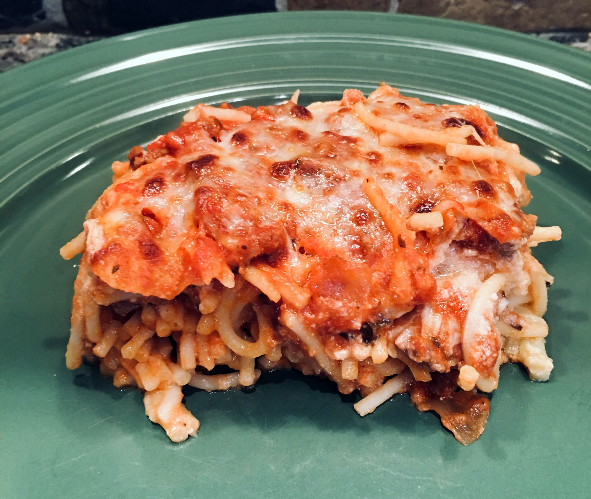 a serving of spaghetti baked with ground beef, 3 cheeses, and a tomato-based sauce on a green plate