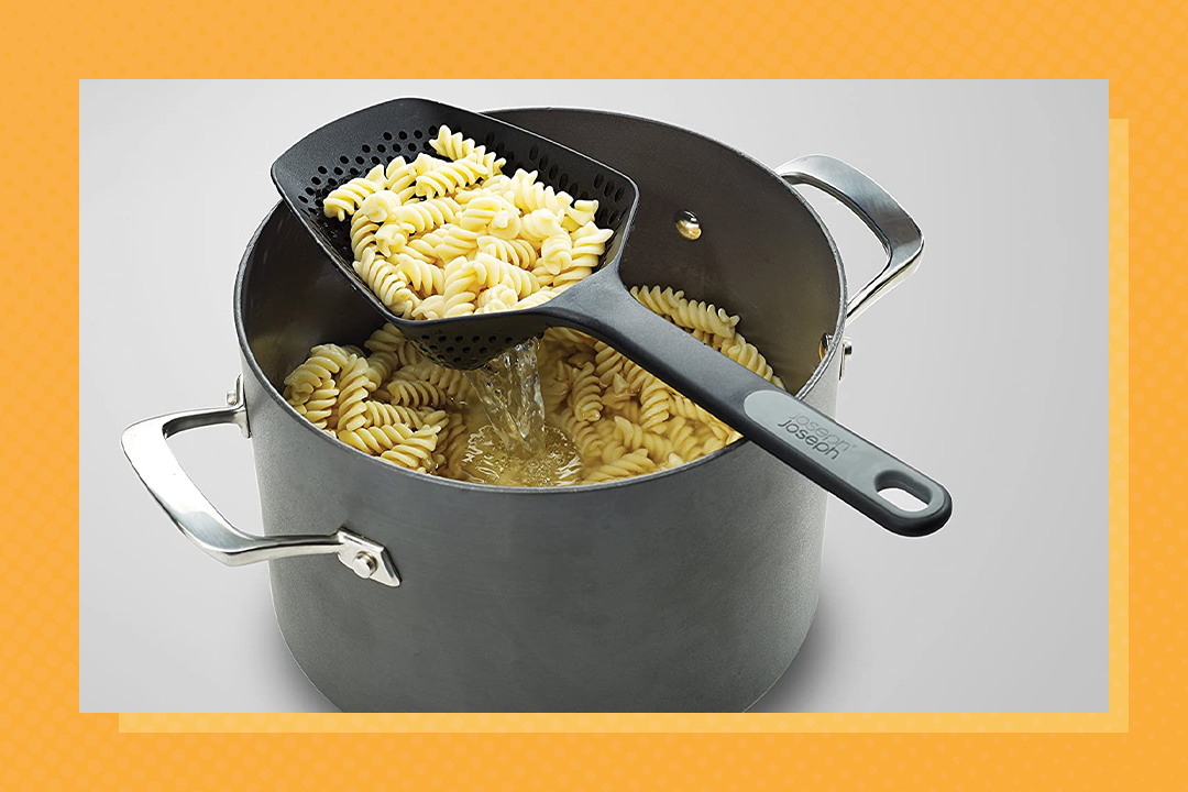 Joseph Joseph Scoop Colander Strainer Slotted Spoon sitting over a pot of cooked pasta