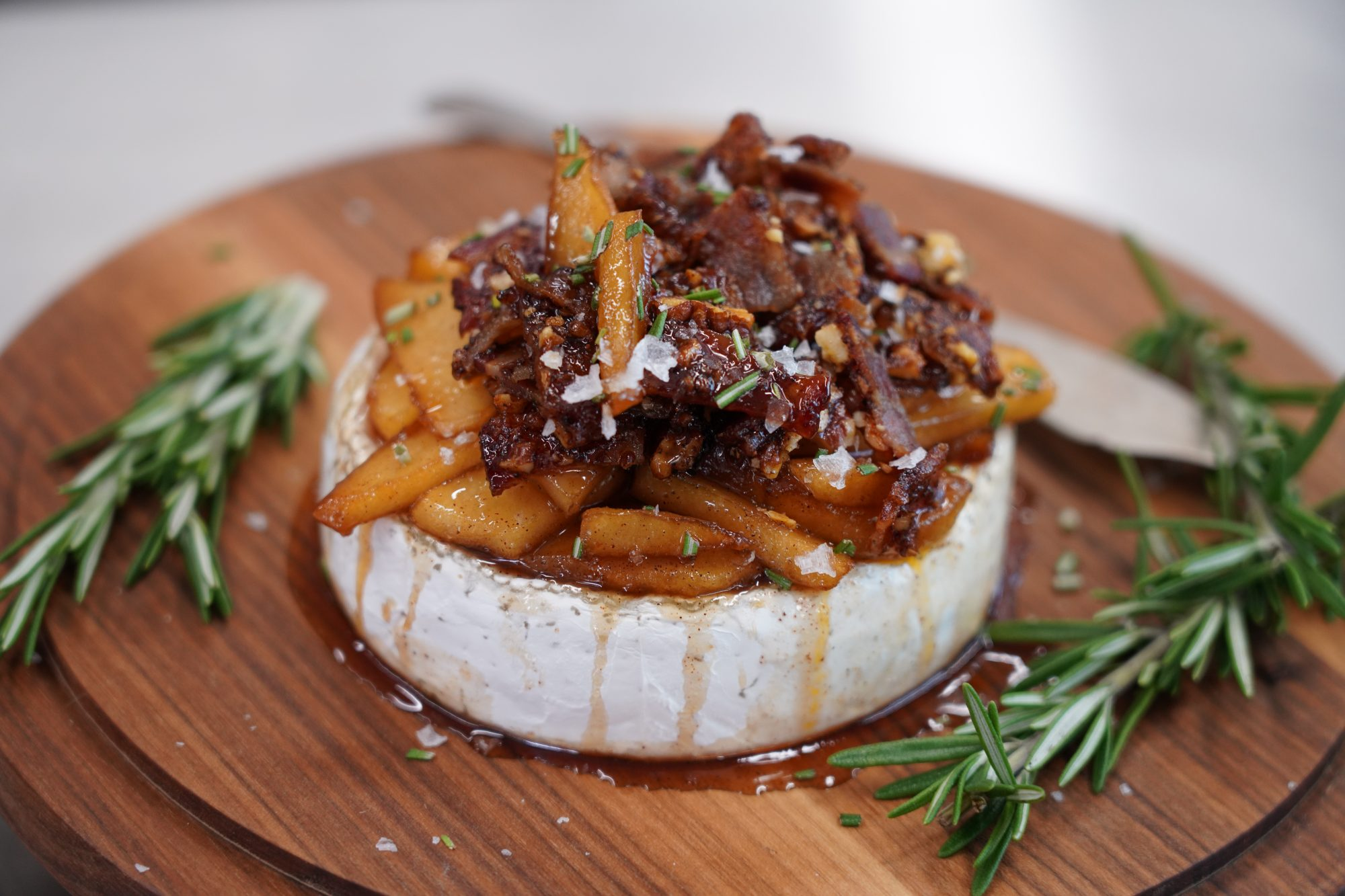 portrait shot apple and bacon-topped brie