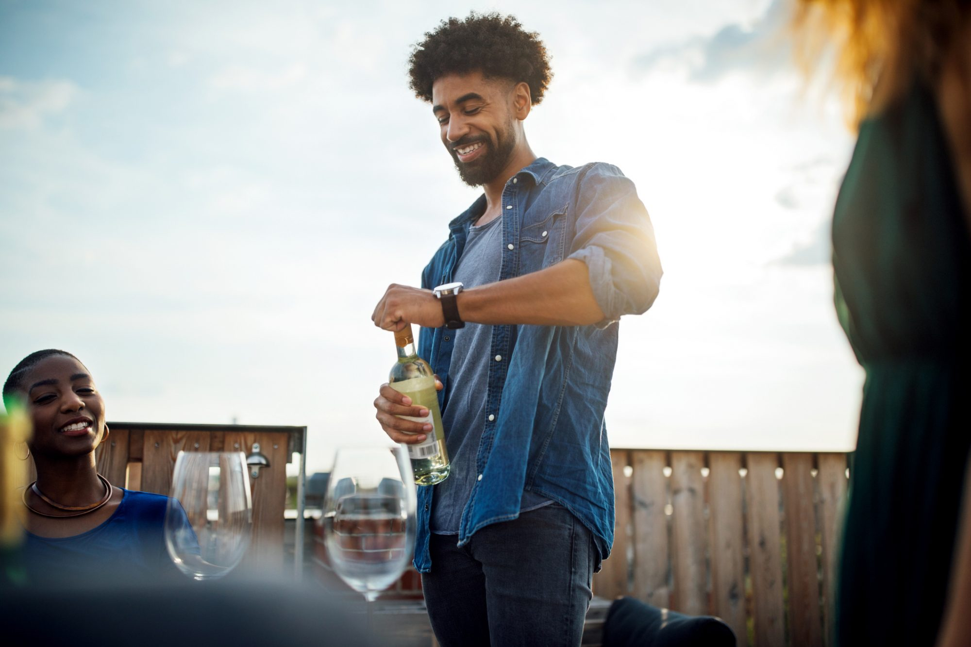 Young man opening wine bottle at rooftop party