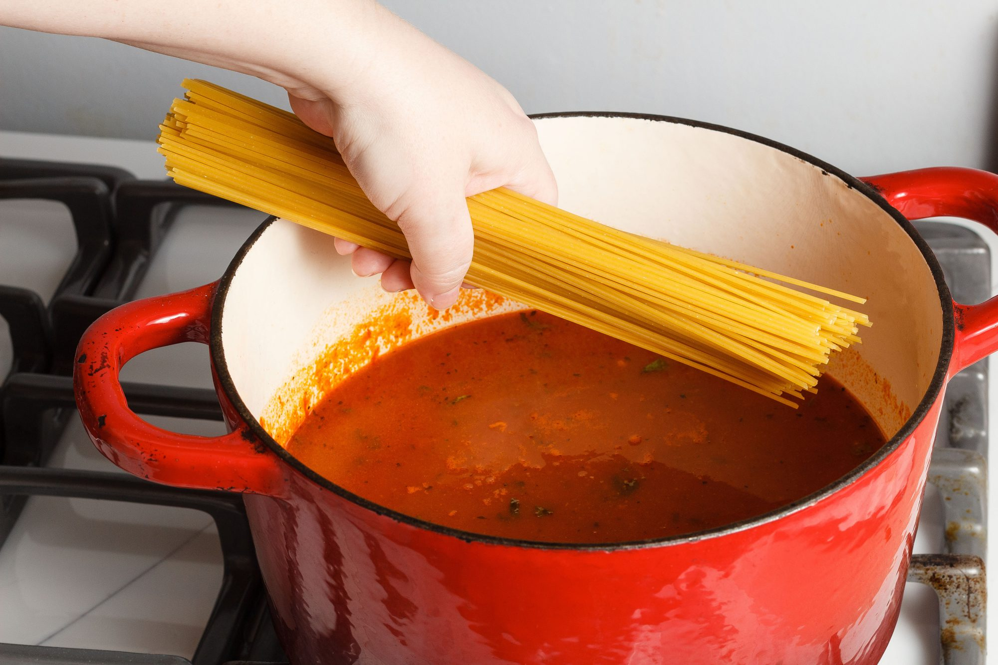 a white woman's hand holds a pound of spaghetti above a Dutch oven half full with spaghetti sauce