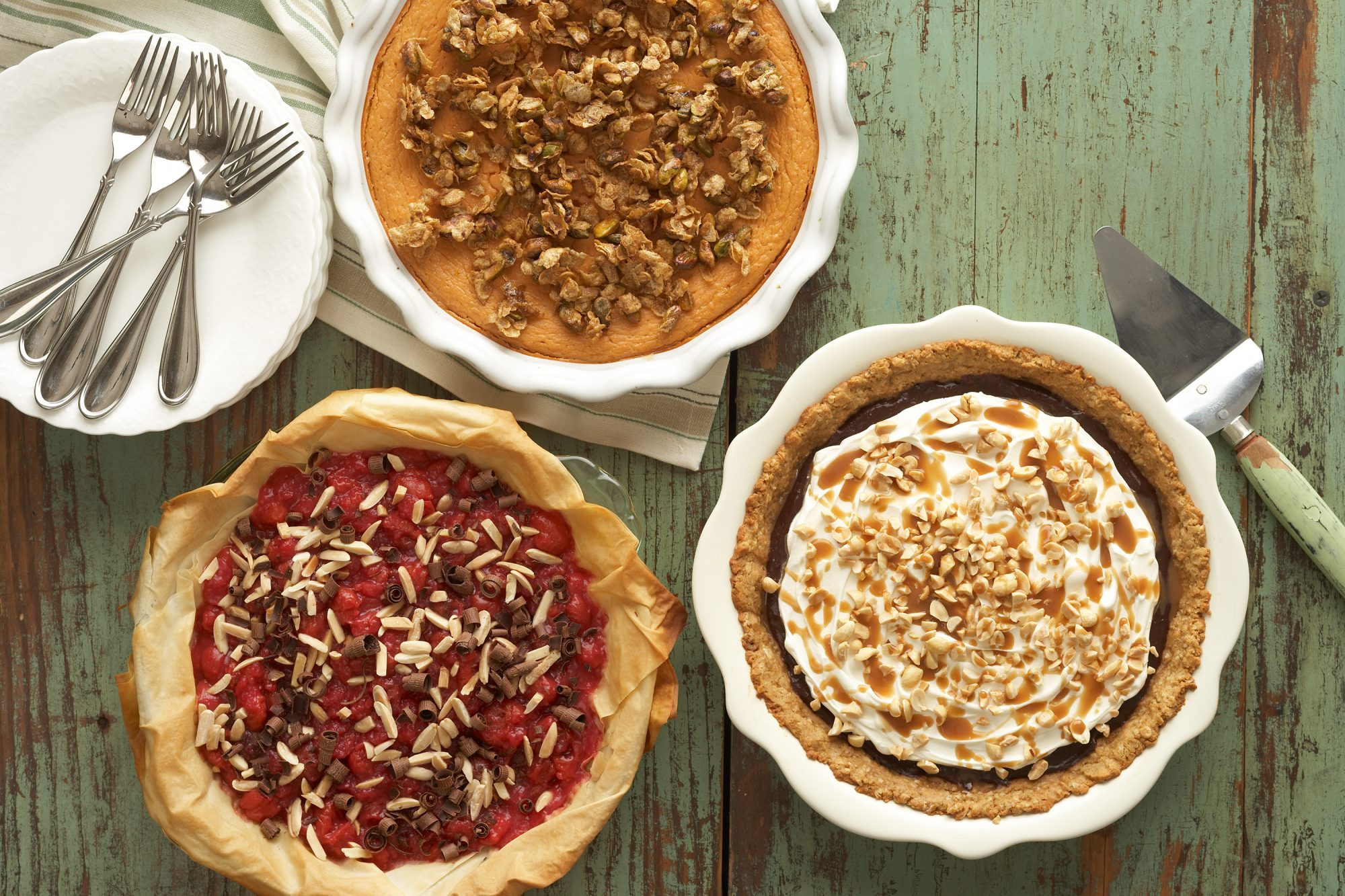 three different pies on wooden table with servingware