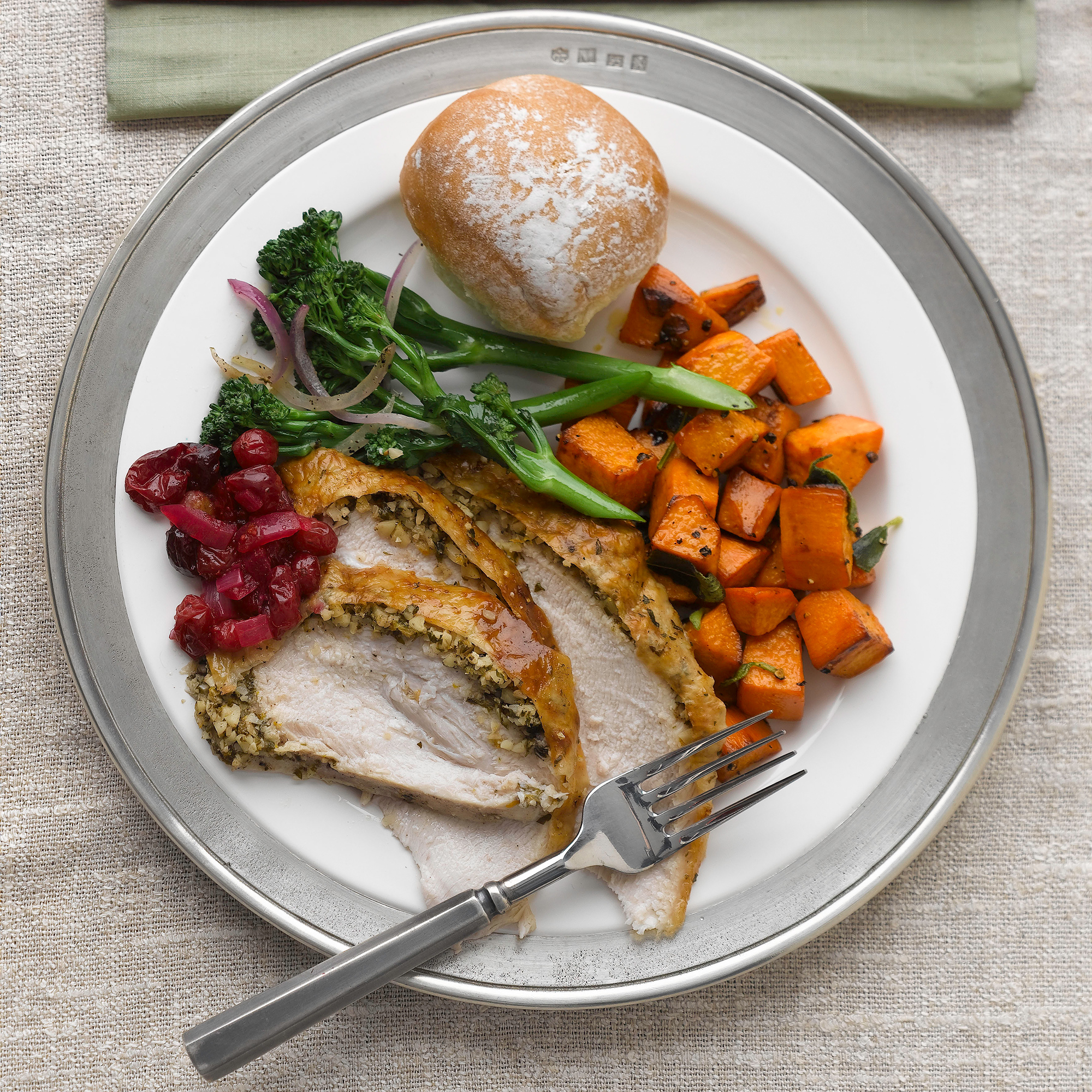 plate with turkey breast, broccoli, sweet potatoes, cranberry sauce, and rolls