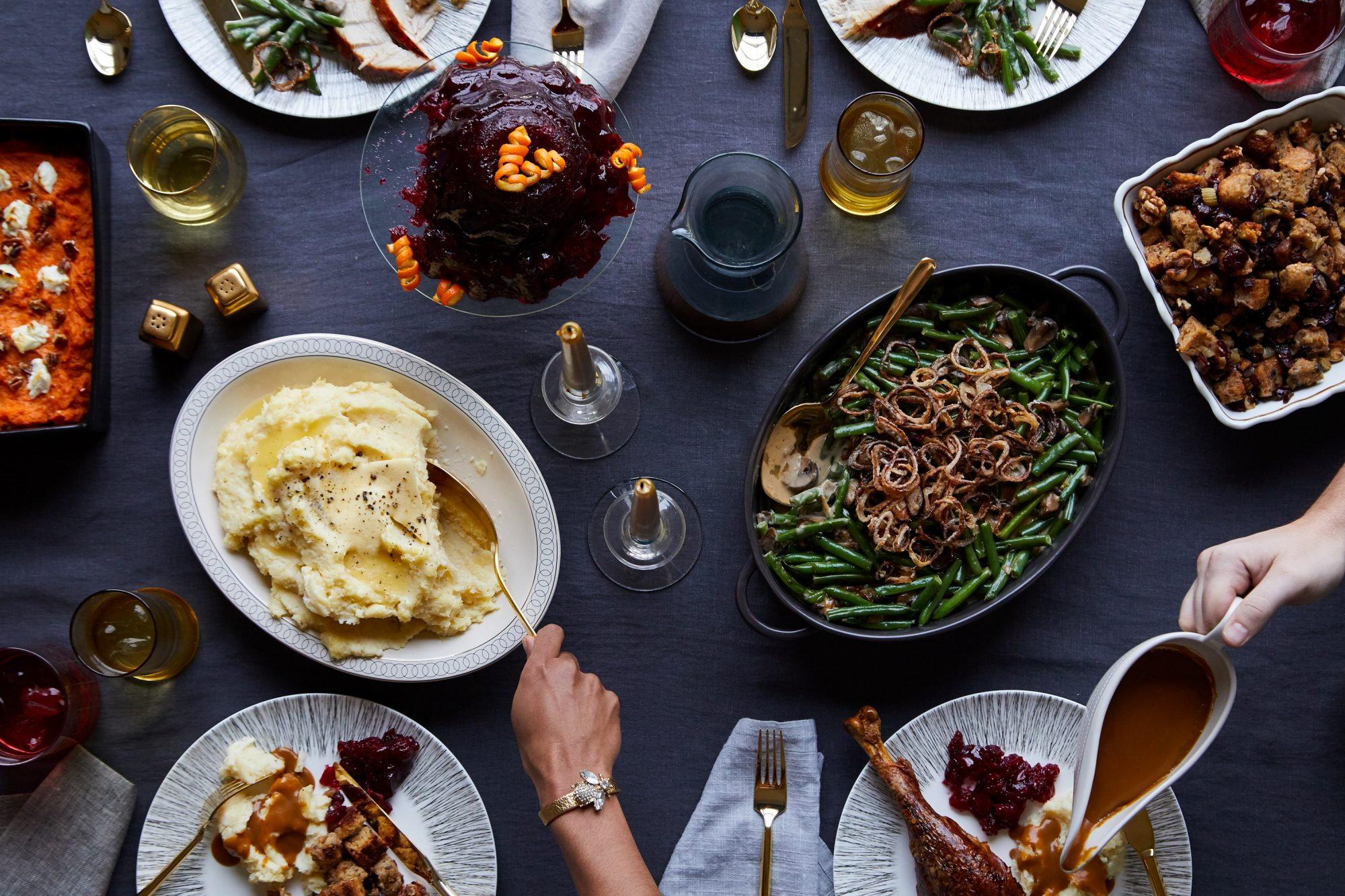 people reaching for side dishes around thanksgiving table