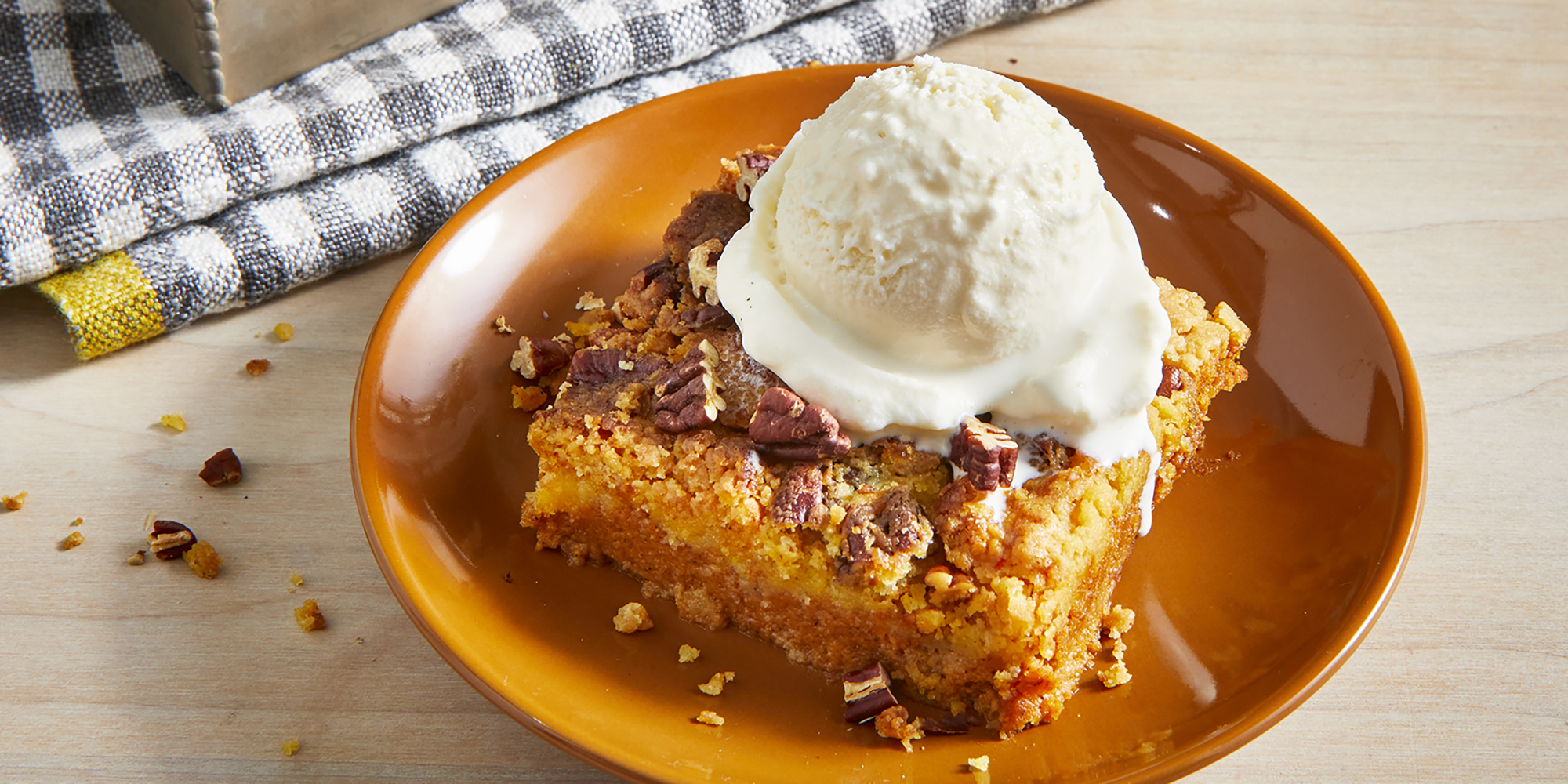 A single square slice of pumpkin crunch cake is plated on a small burnt orange plate and topped with a melting scoop of vanilla ice cream.The remaining cake sits in the baking dish in the background.