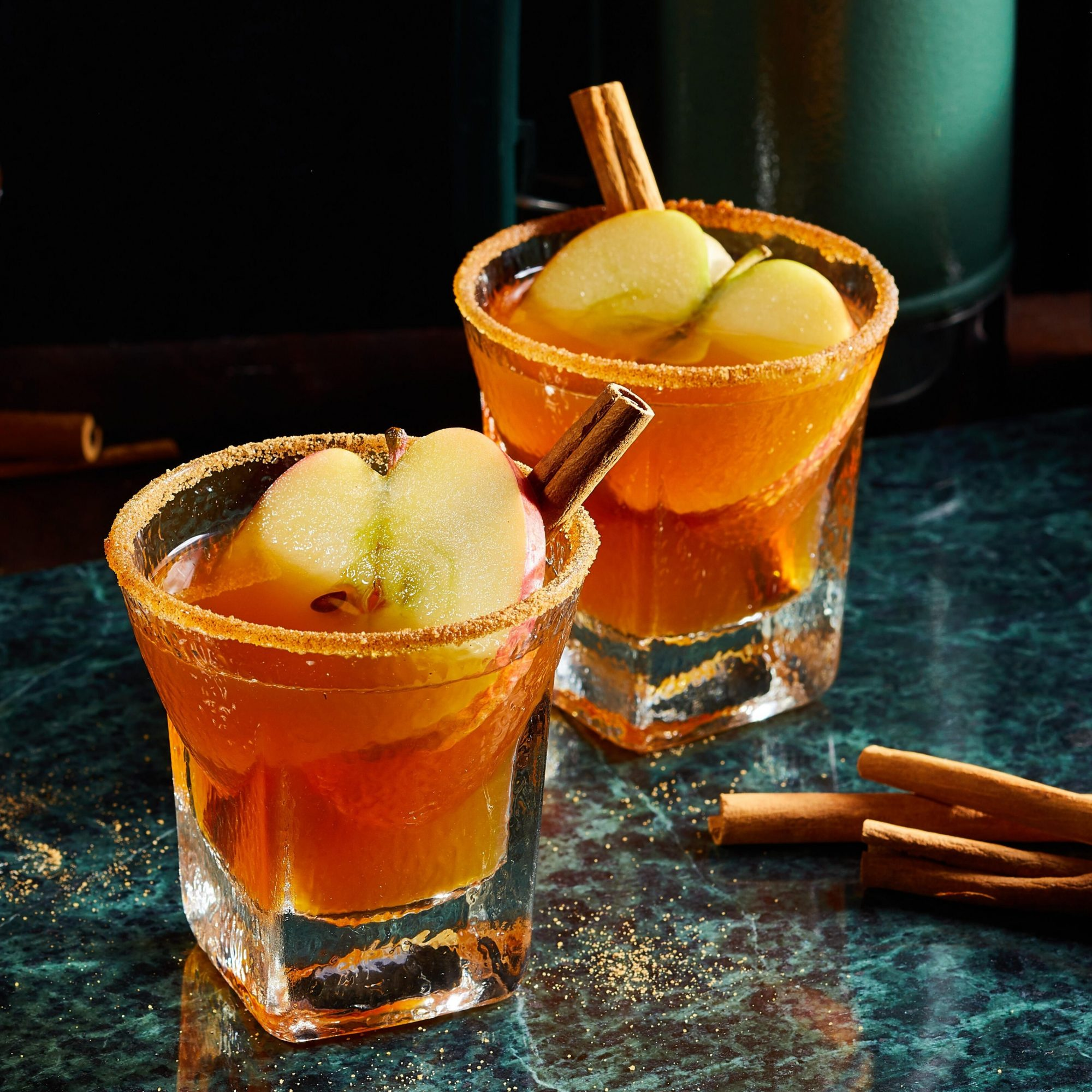two whisky glasses rimmed with cinnamon sugar, filled with Cider-Bourbon Thermos Cocktail recipe, and garnished with cinnamon sticks and apple slices