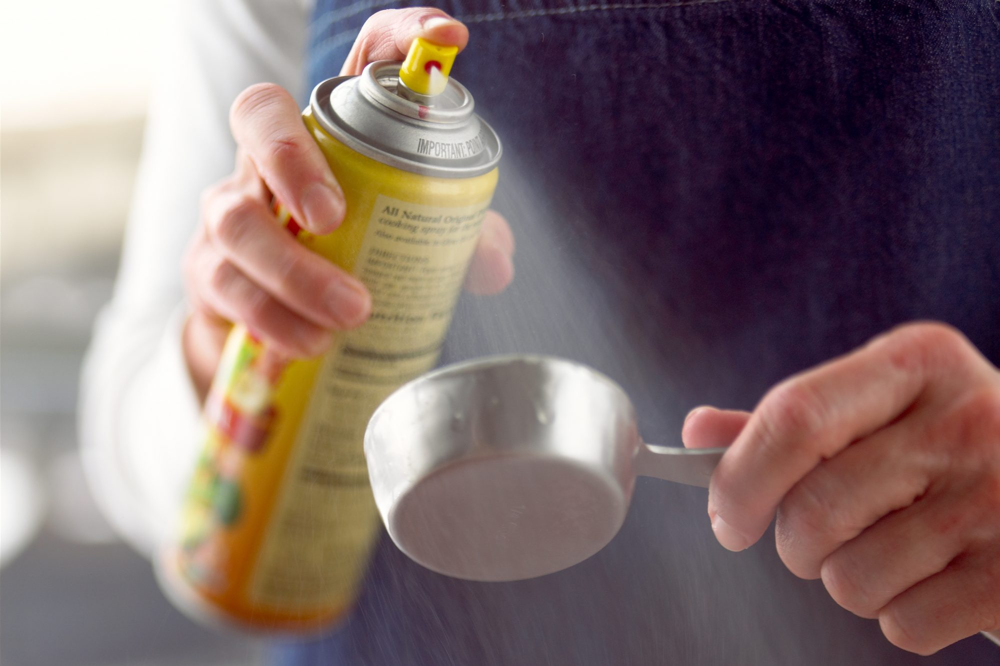 person spraying cooking spray on metal dry measuring cup