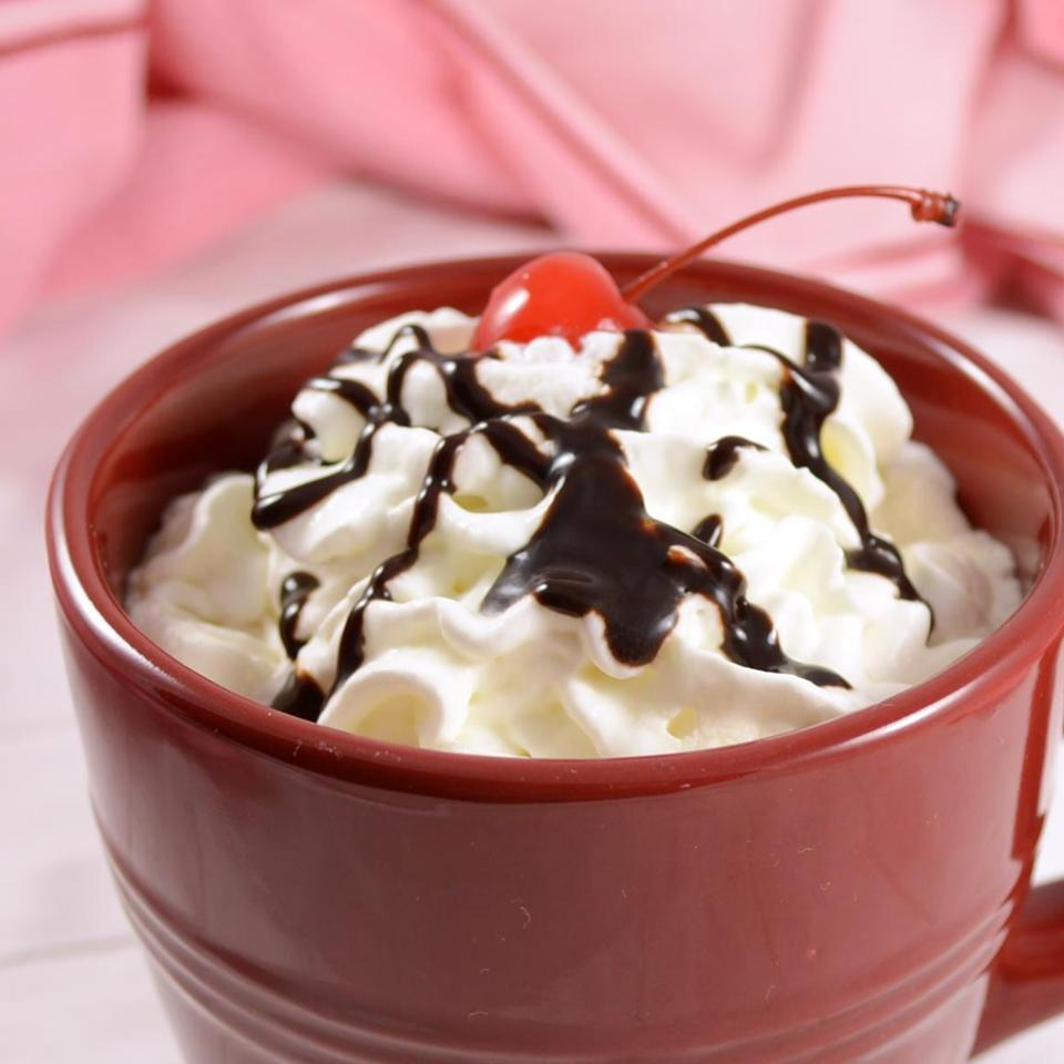 red mug of homemade Chocolate Coffee Kiss drink topped with whipped cream and chocolate syrup
