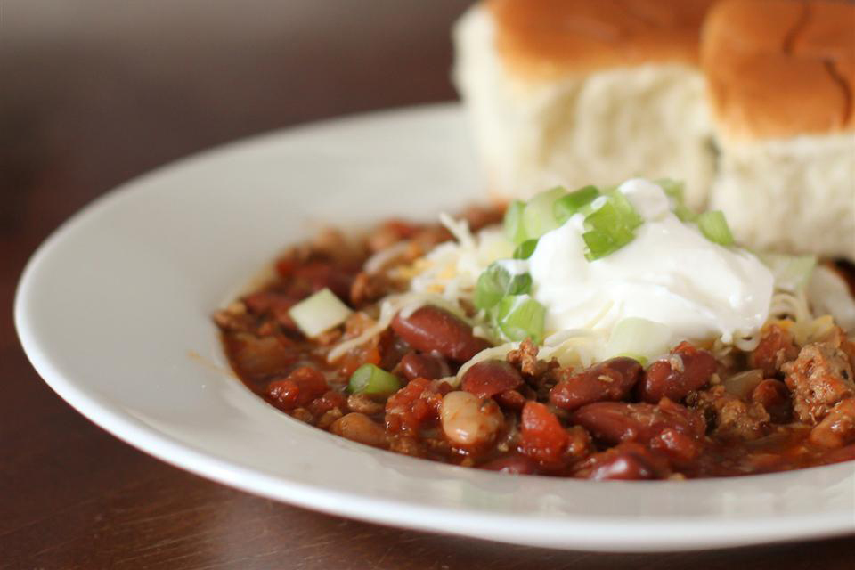 a bowl of Simple Turkey Chili topped with sour cream and green onions and cheese with two rolls on the bowl rim