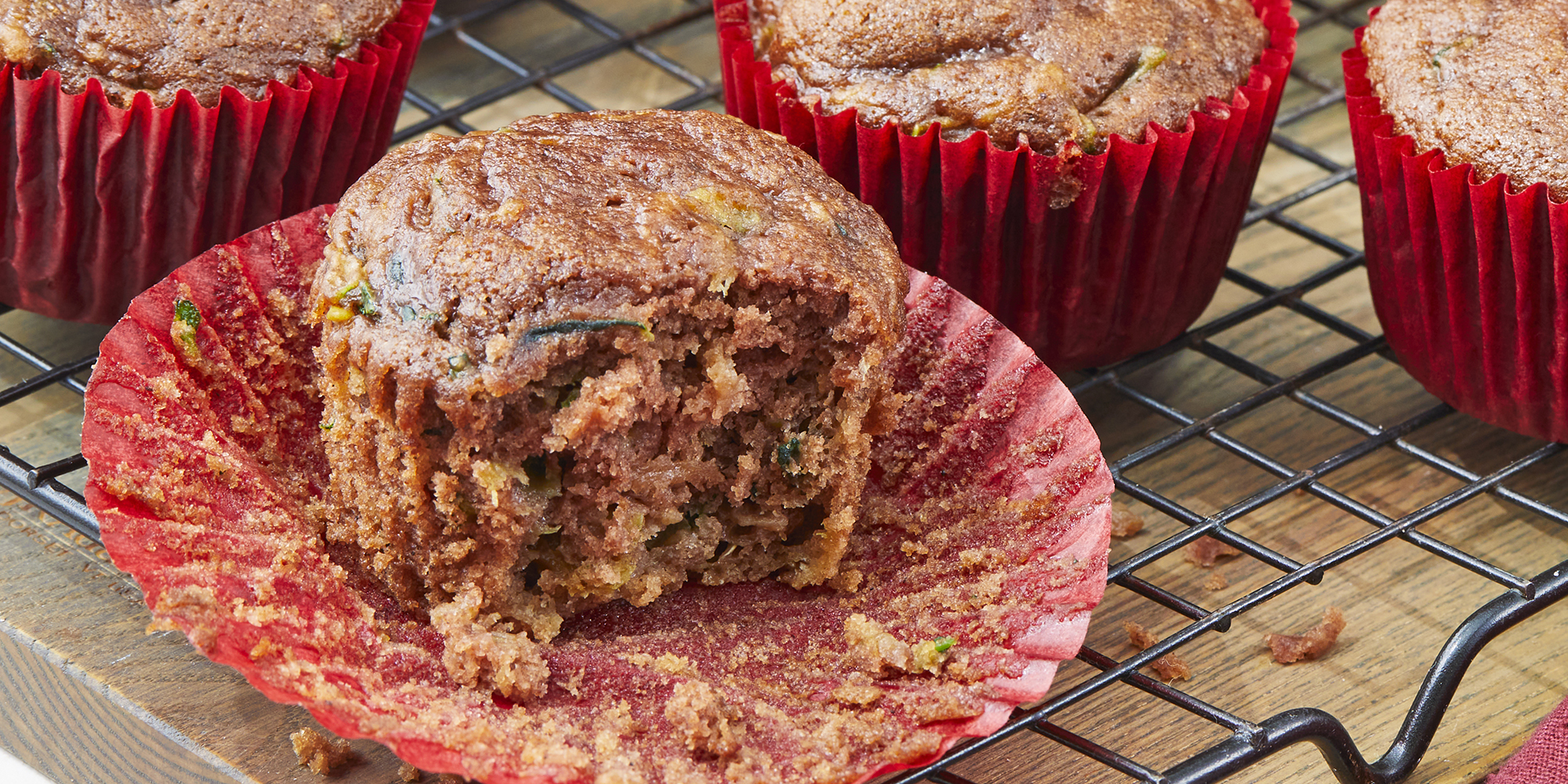 looking into an apple cinnamon muffin sitting on a cooling rack with a bite out.