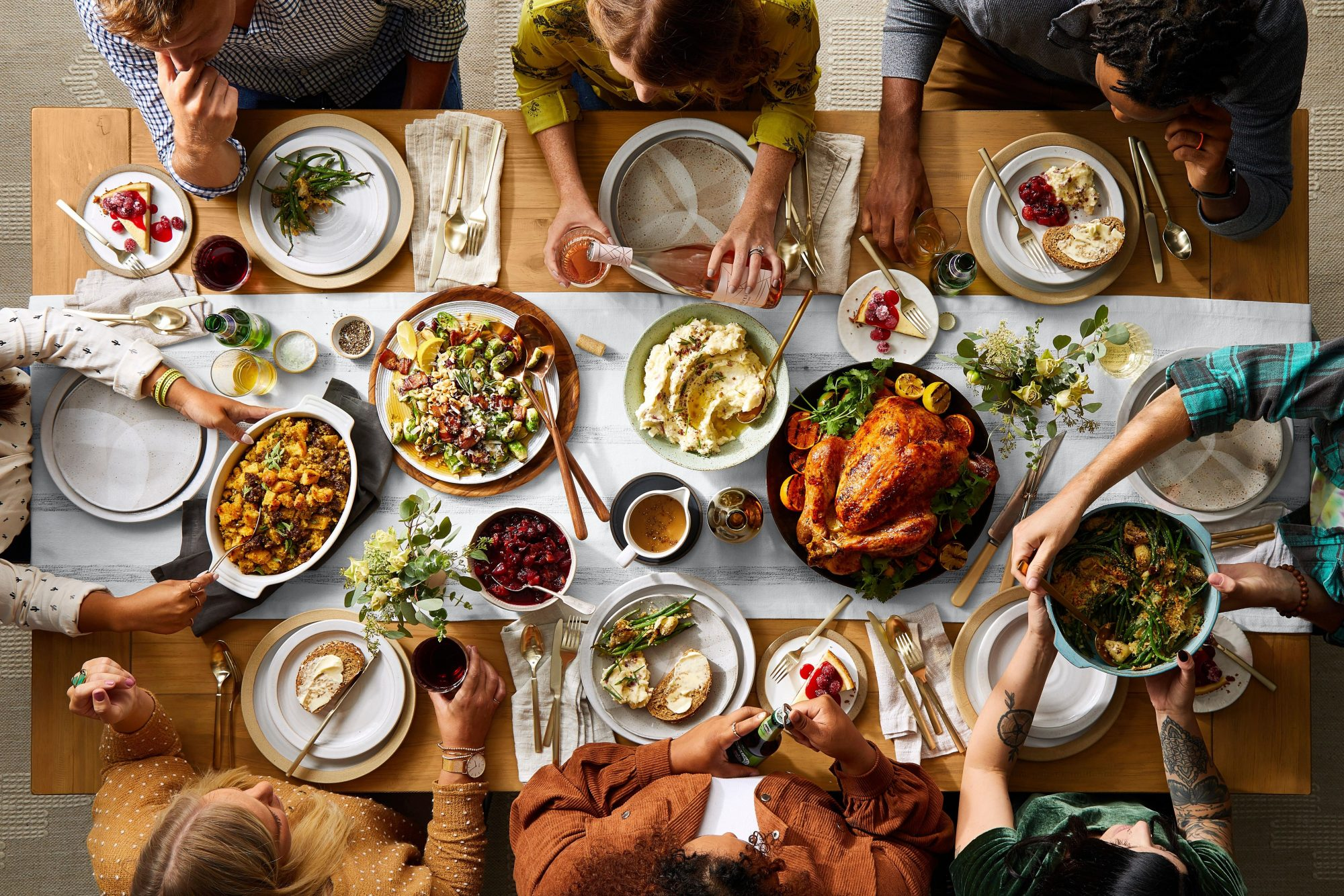 overhead view of friends gathered around a table set with a Thanksgiving dinner