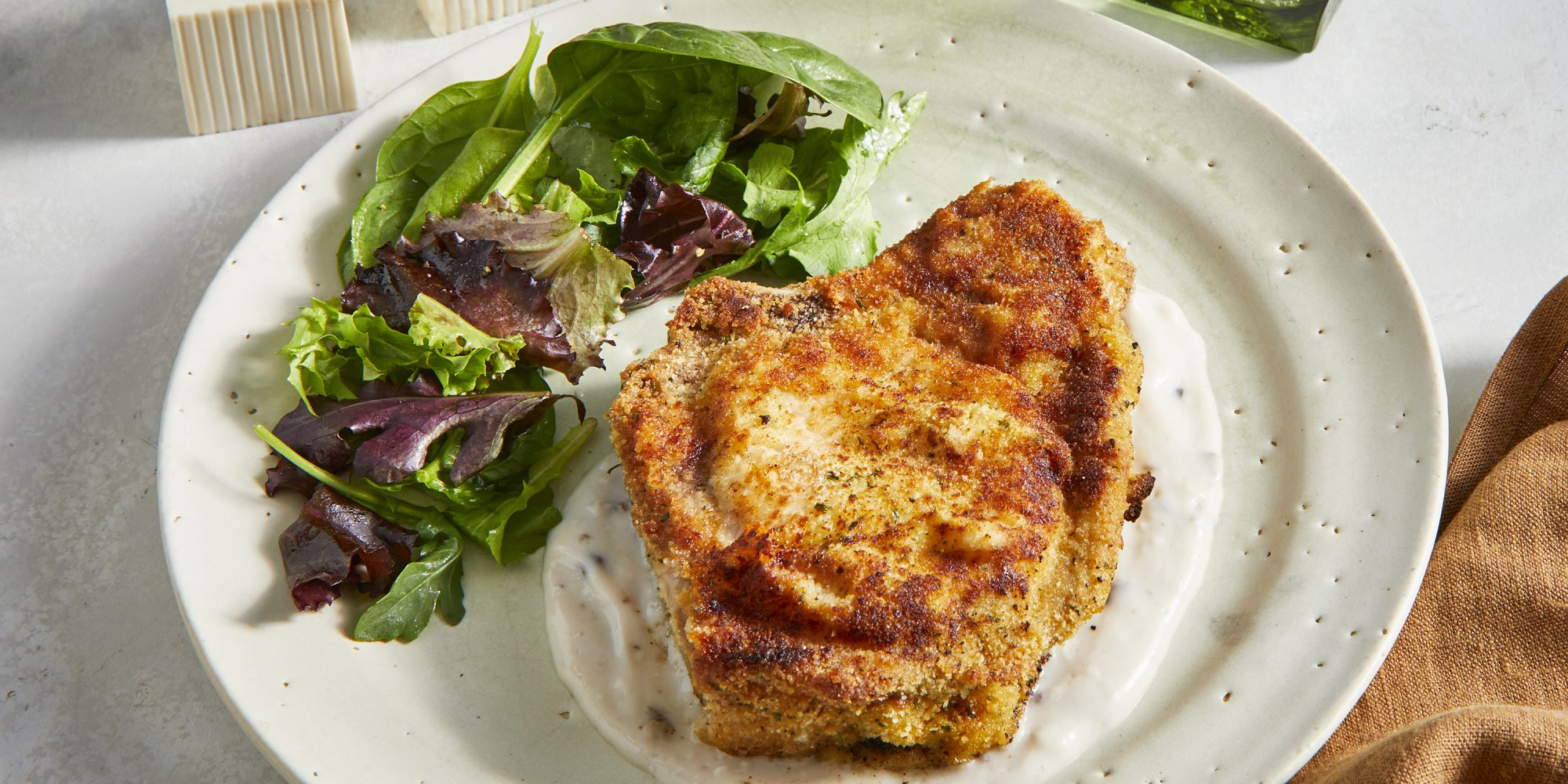 High angle view on a baked pork chop plated on a mushroom cream sauce and served with dressed mixed greens.