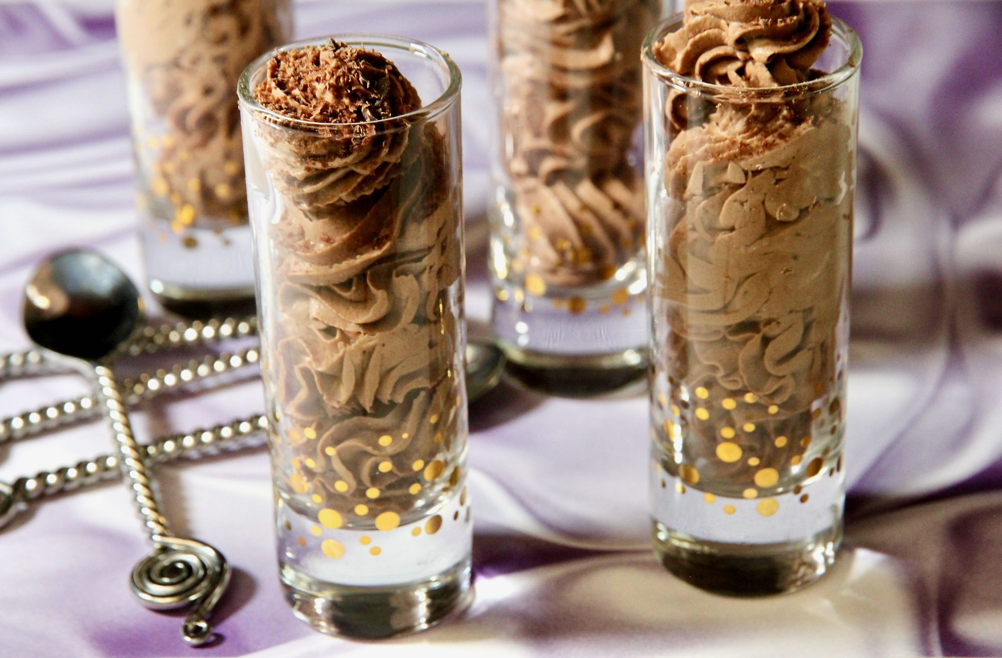 tall tumbler glasses with chocolate mousse on purple cloth
