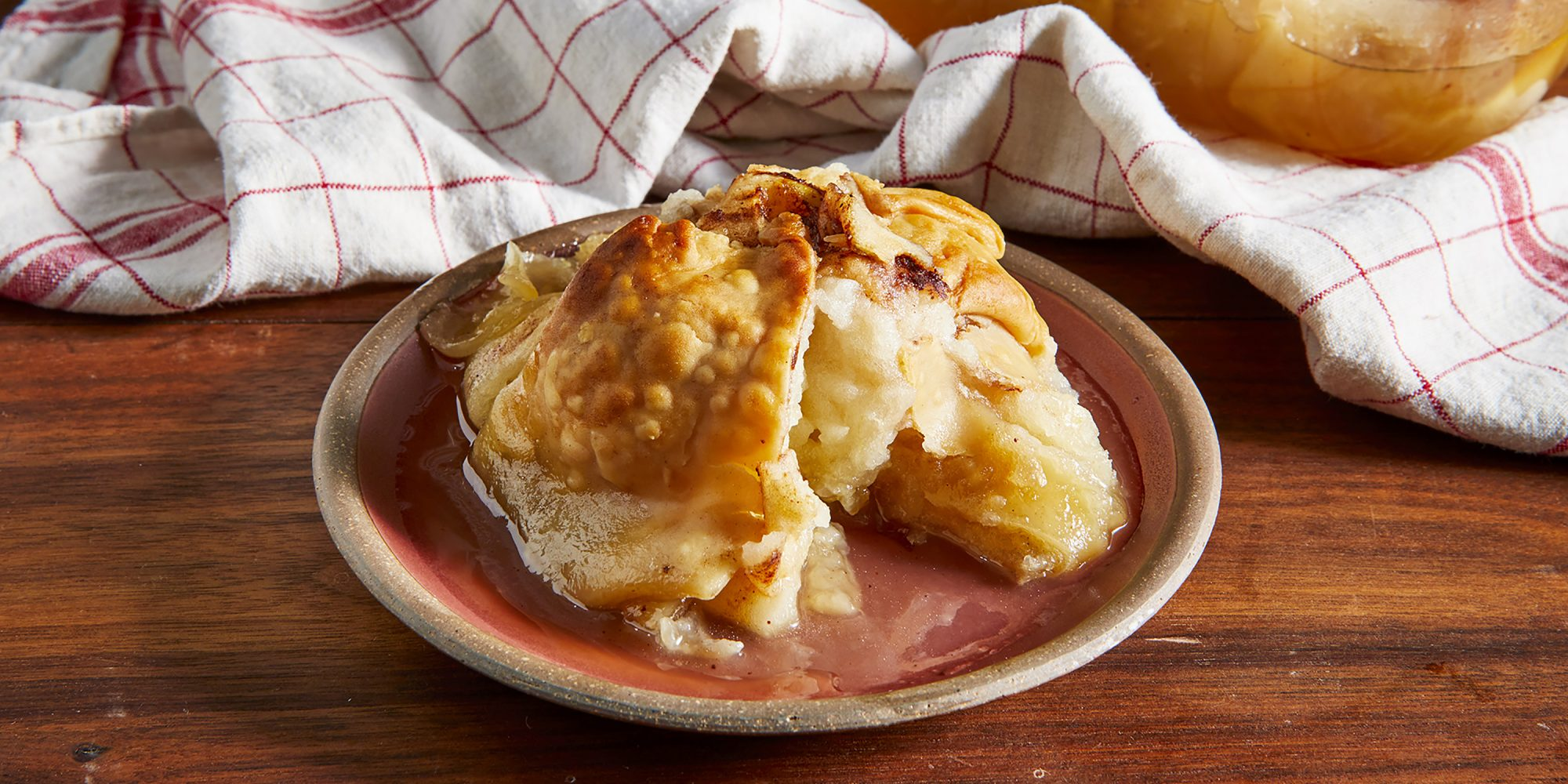Looking into a single plated old fashioned apple dumpling with a bite taken out.