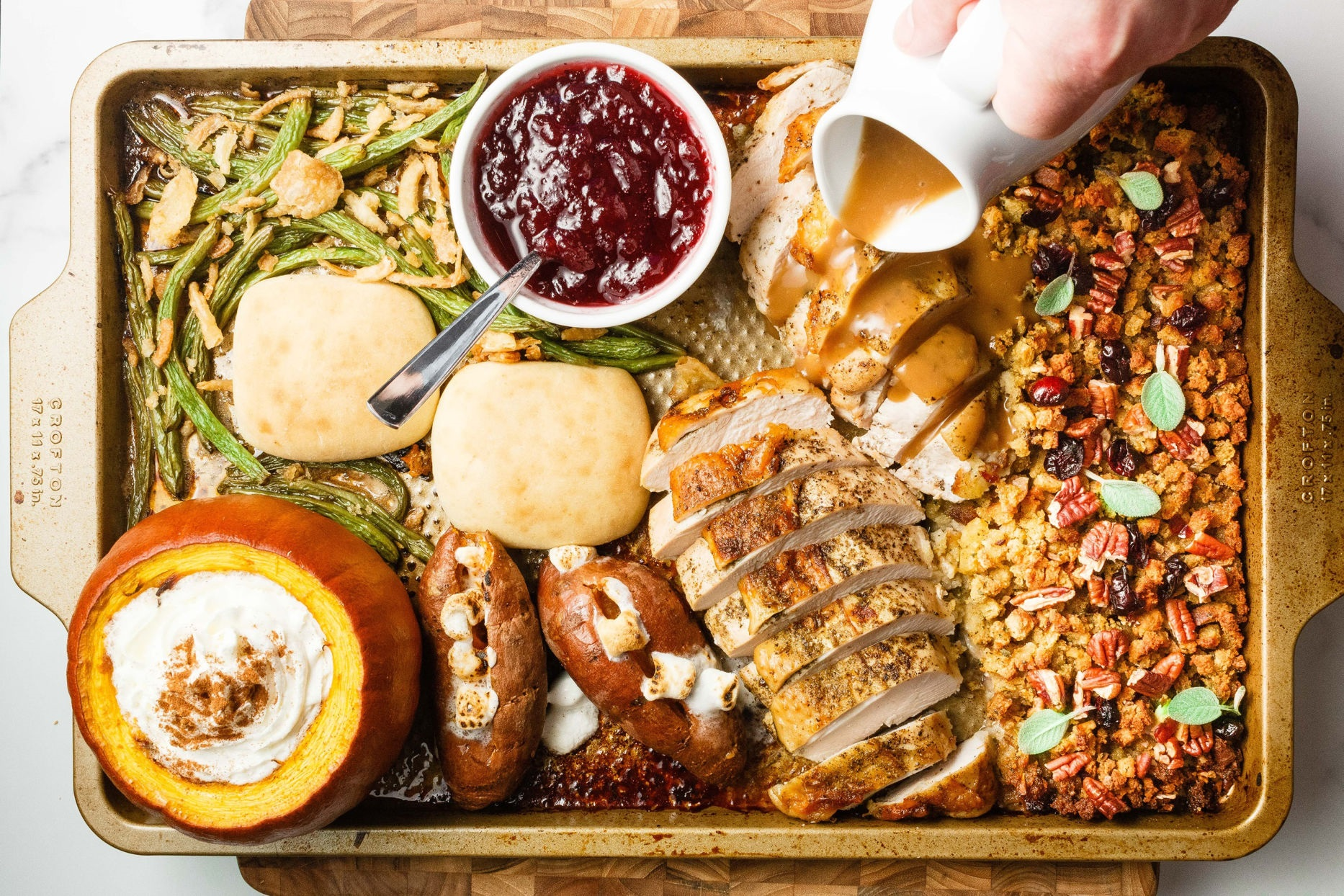 overhead view of Thanksgiving Sheet Pan Meal for Two recipe with turkey breast, stuffing, sweet potatoes, green beans, pumpkin dessert, cranberry sauce, and gravy