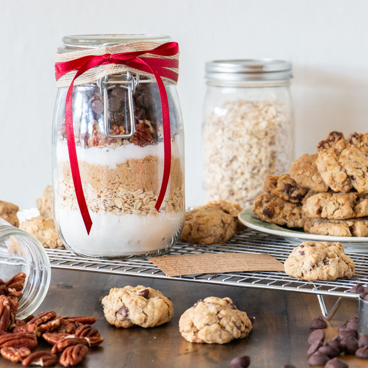 jar of homemade Cowboy Cookie Mix in a Jar recipe displayed with finish cookies, oats, nuts, and chocolate chips