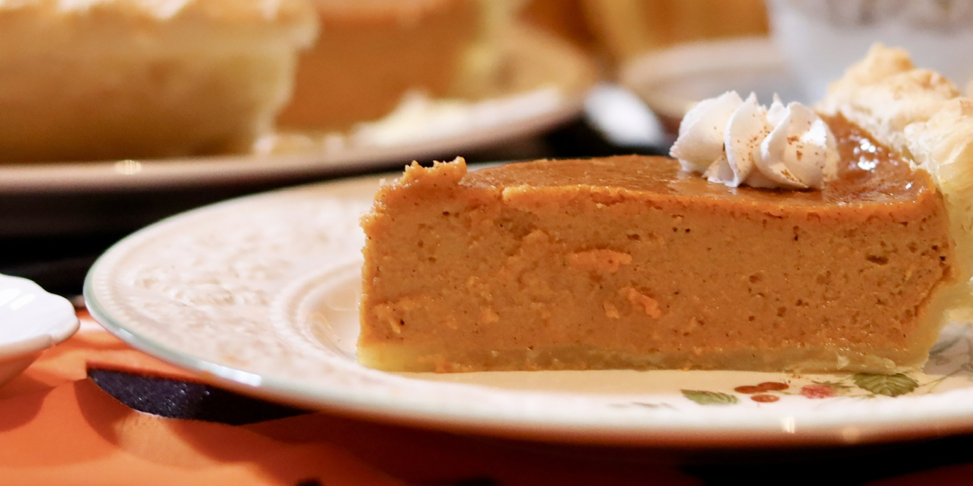 close up on a slice of perfect pumpkin pie topped with a dollop of whipped cream.