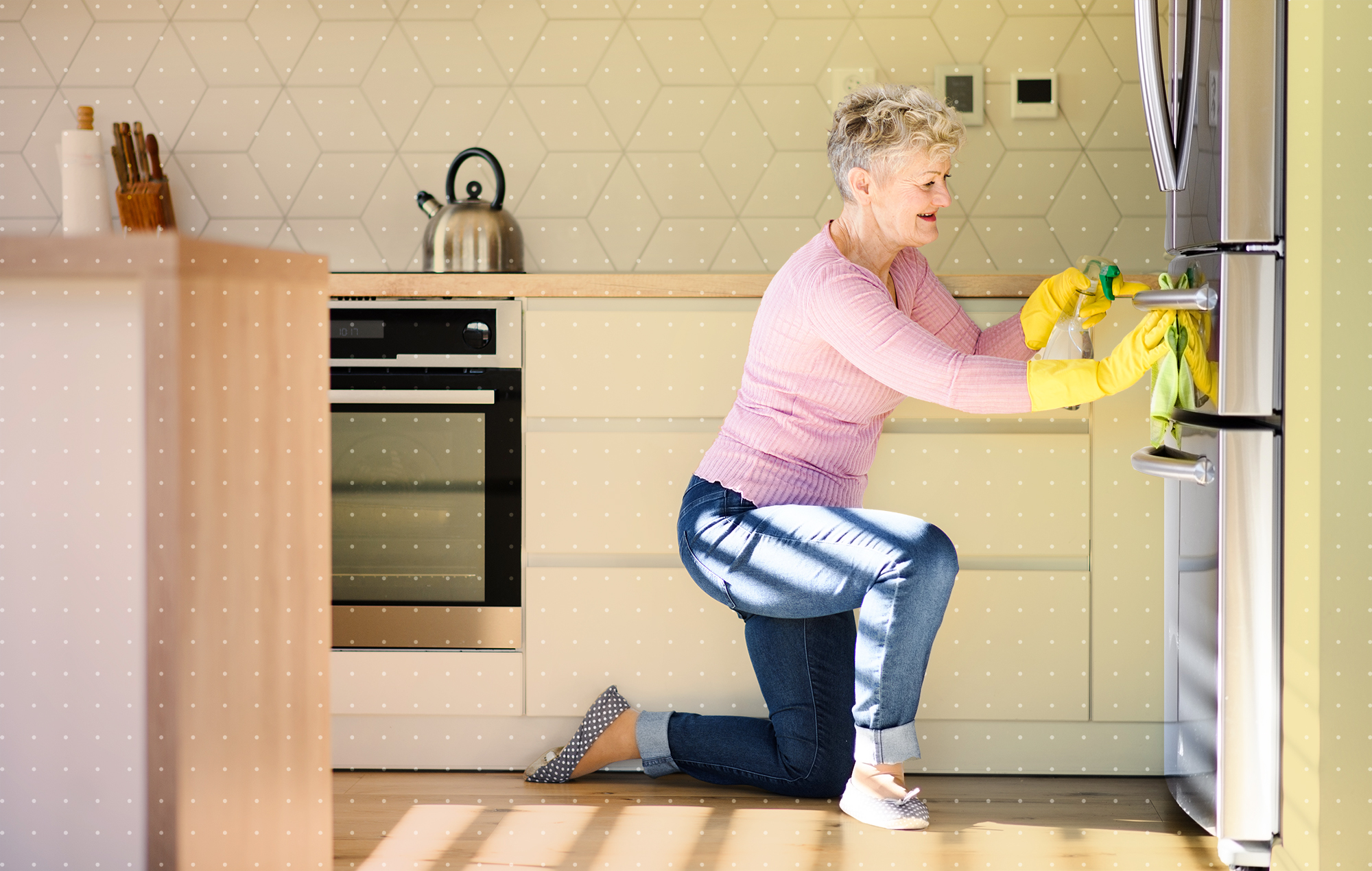 Side view of senior woman indoors at home, cleaning kitchen