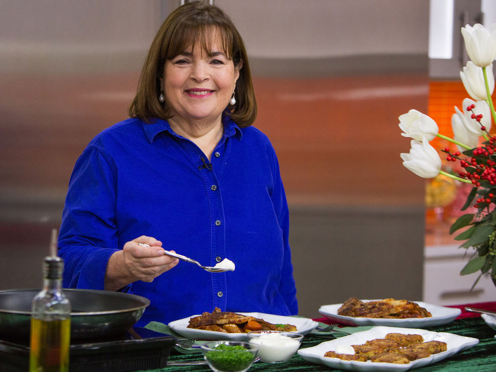 Ina Garten in a blue shirt holding a spoonful of food