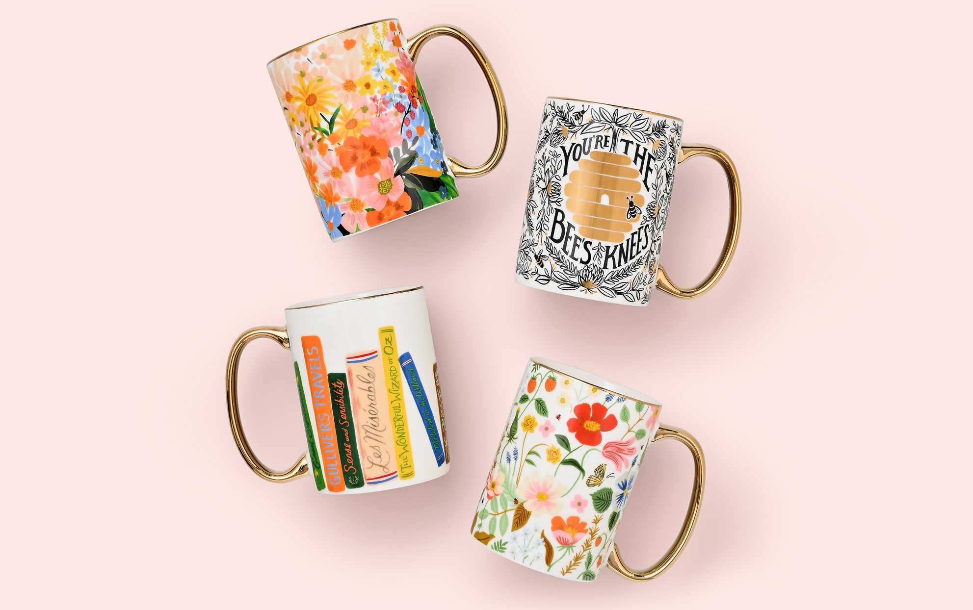Four Rifle Paper Co mugs on a pink background