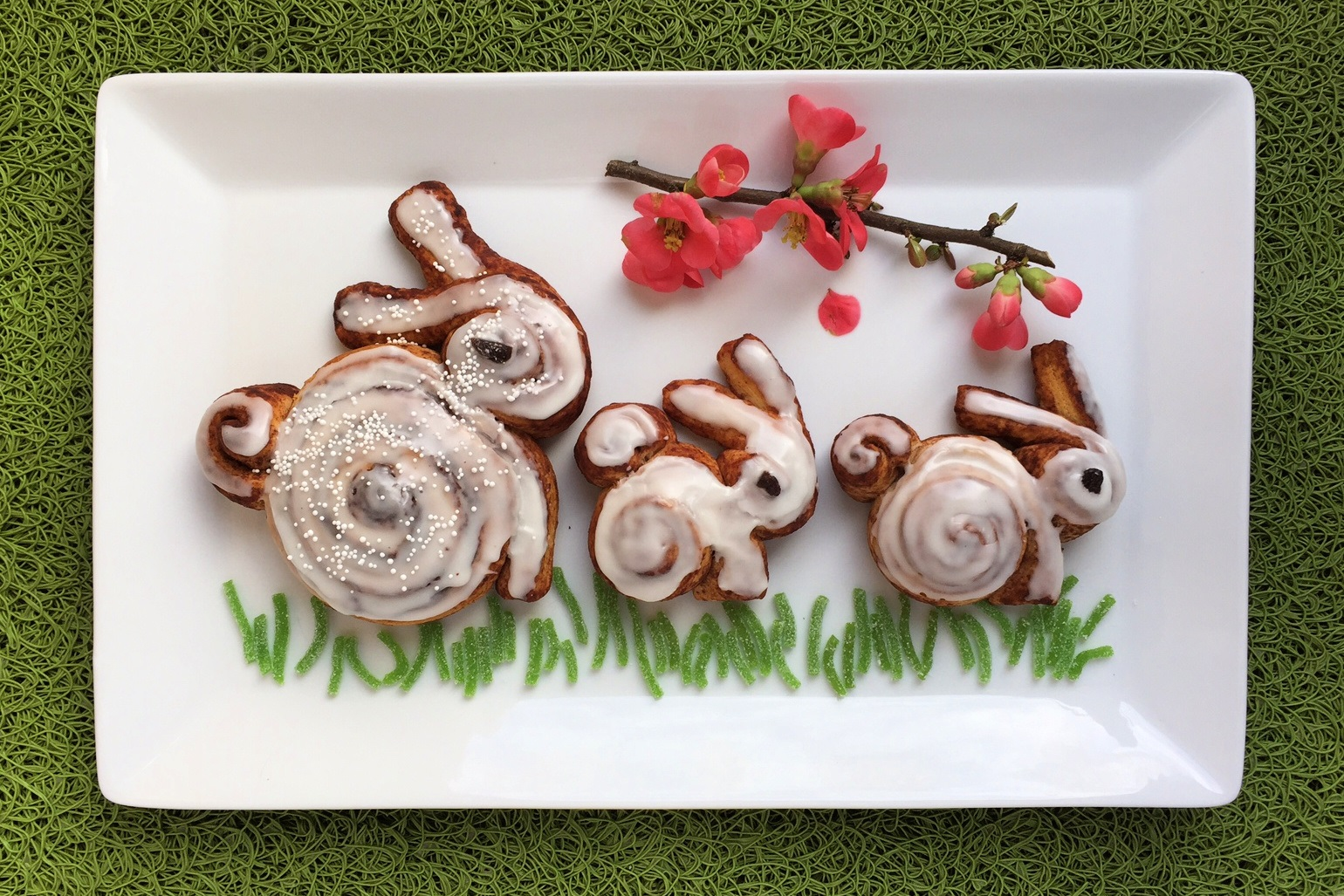 cinnamon roll bunnies displayed on a platter with candy grass and quince blossoms