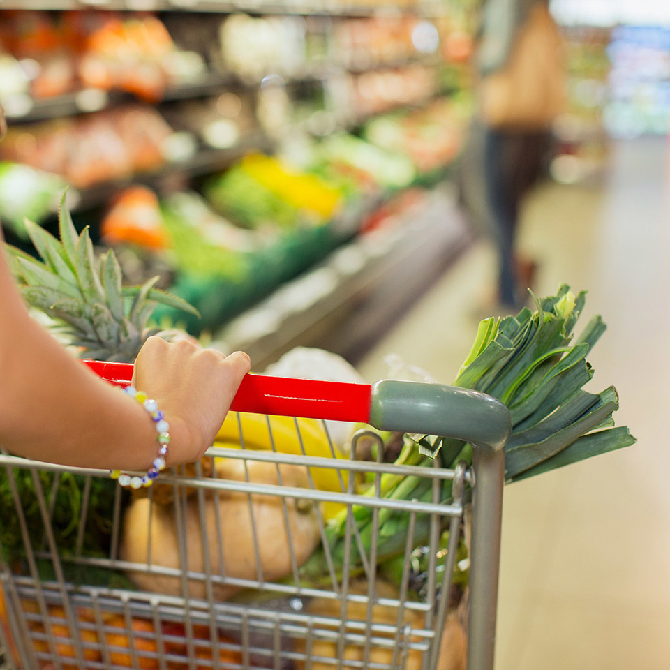 woman pushing grocery cart full of healthy foods