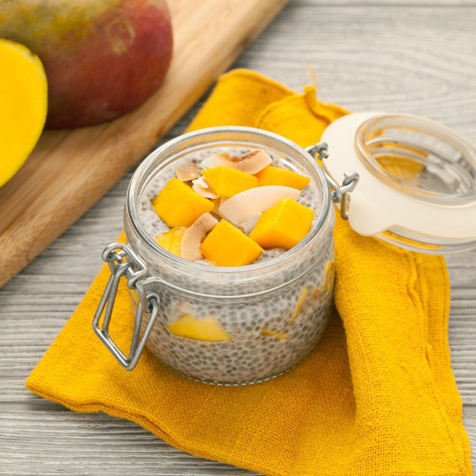 mango chia pudding in mason jar with yellow napkin on wooden background