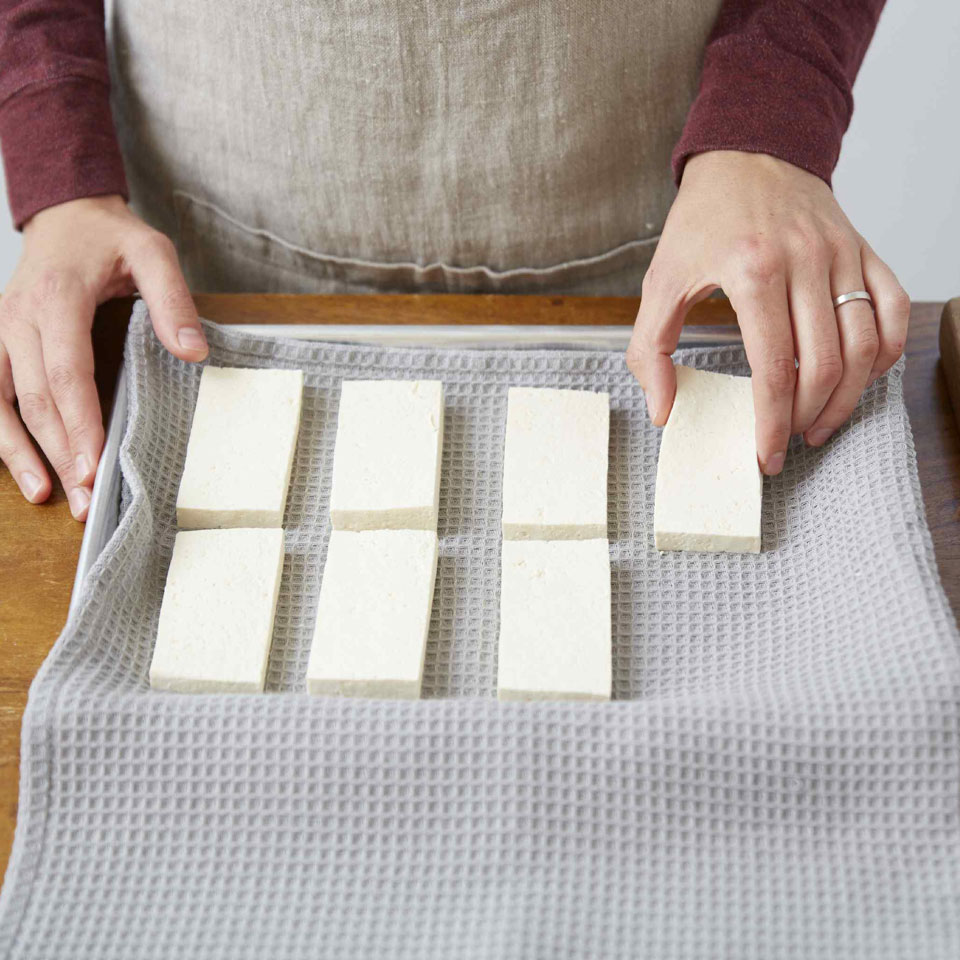 Placing tofu on a towel-lined sheet pan