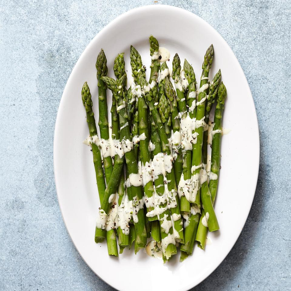 asparagus on a plate drizzled in hollondaise sauce